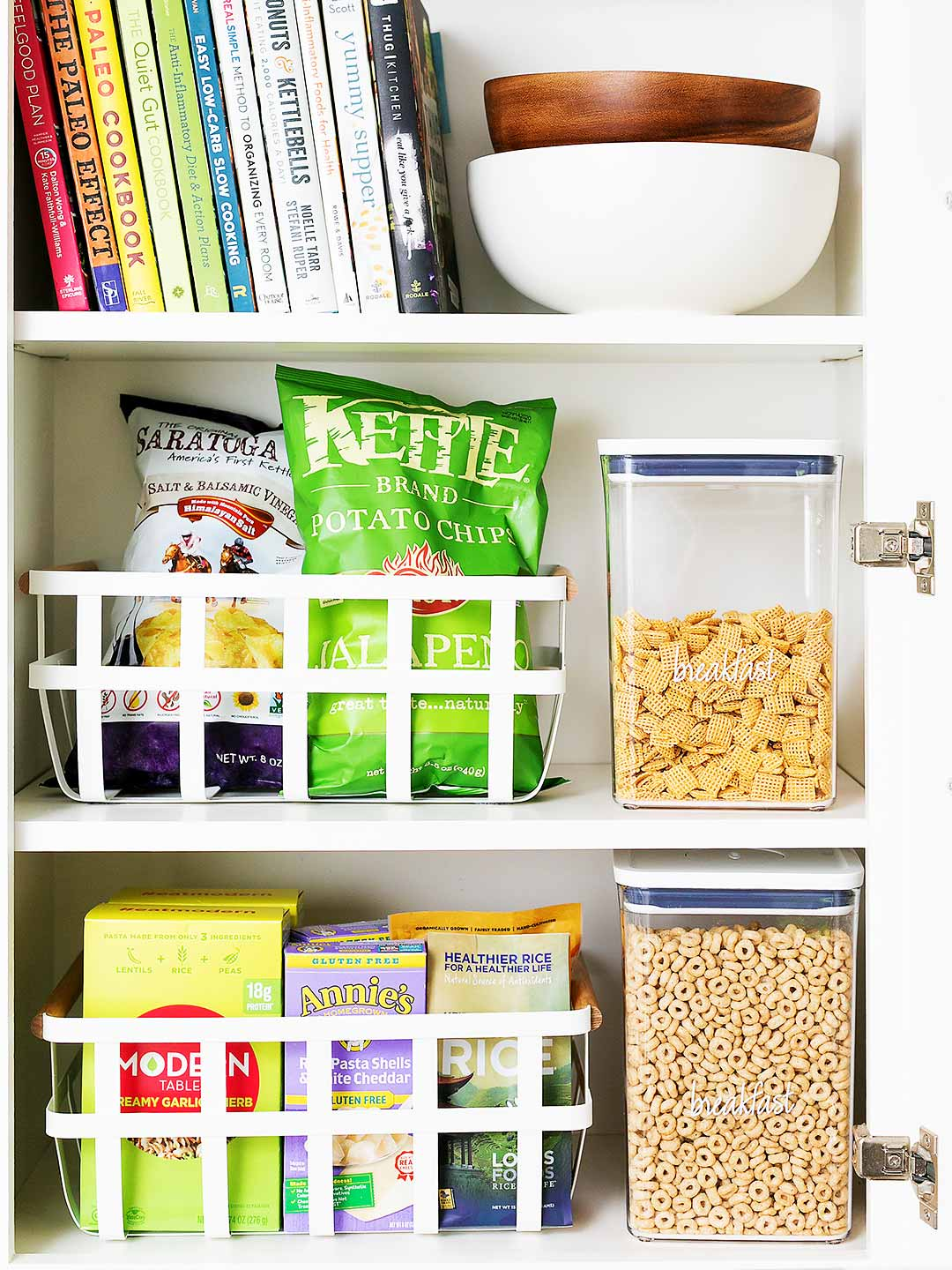 Cookbooks and cooking ingredients organized on kitchen shelves by type and color