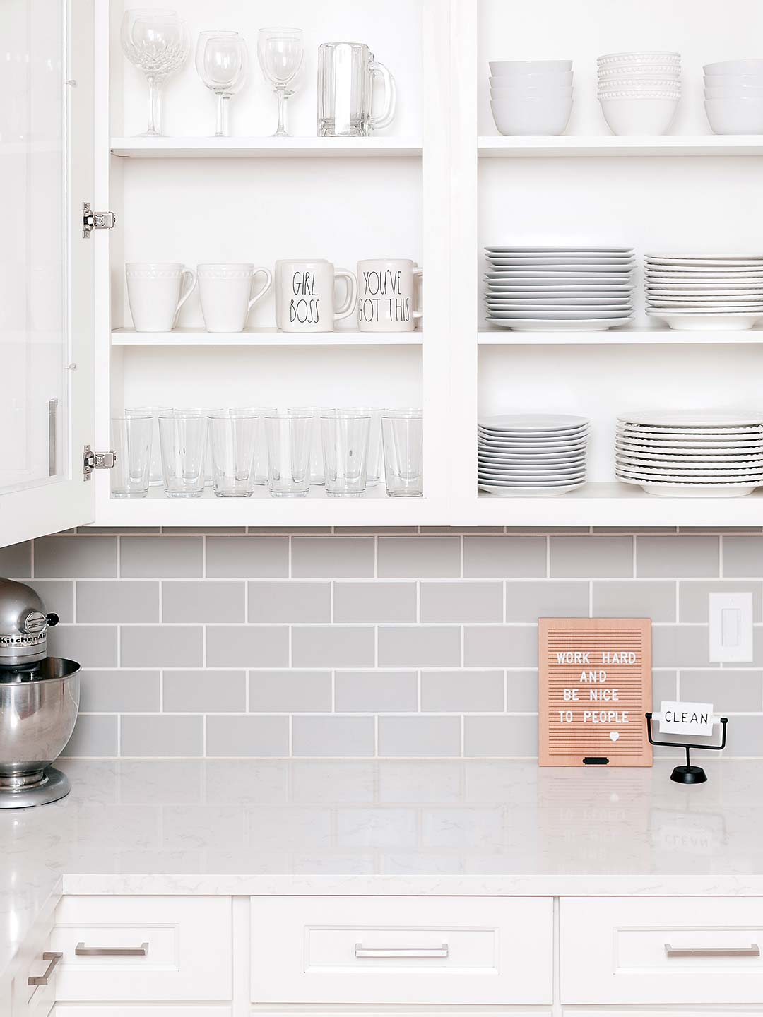 Full dinnerware set organizing in kitchen cabinets with glass doors
