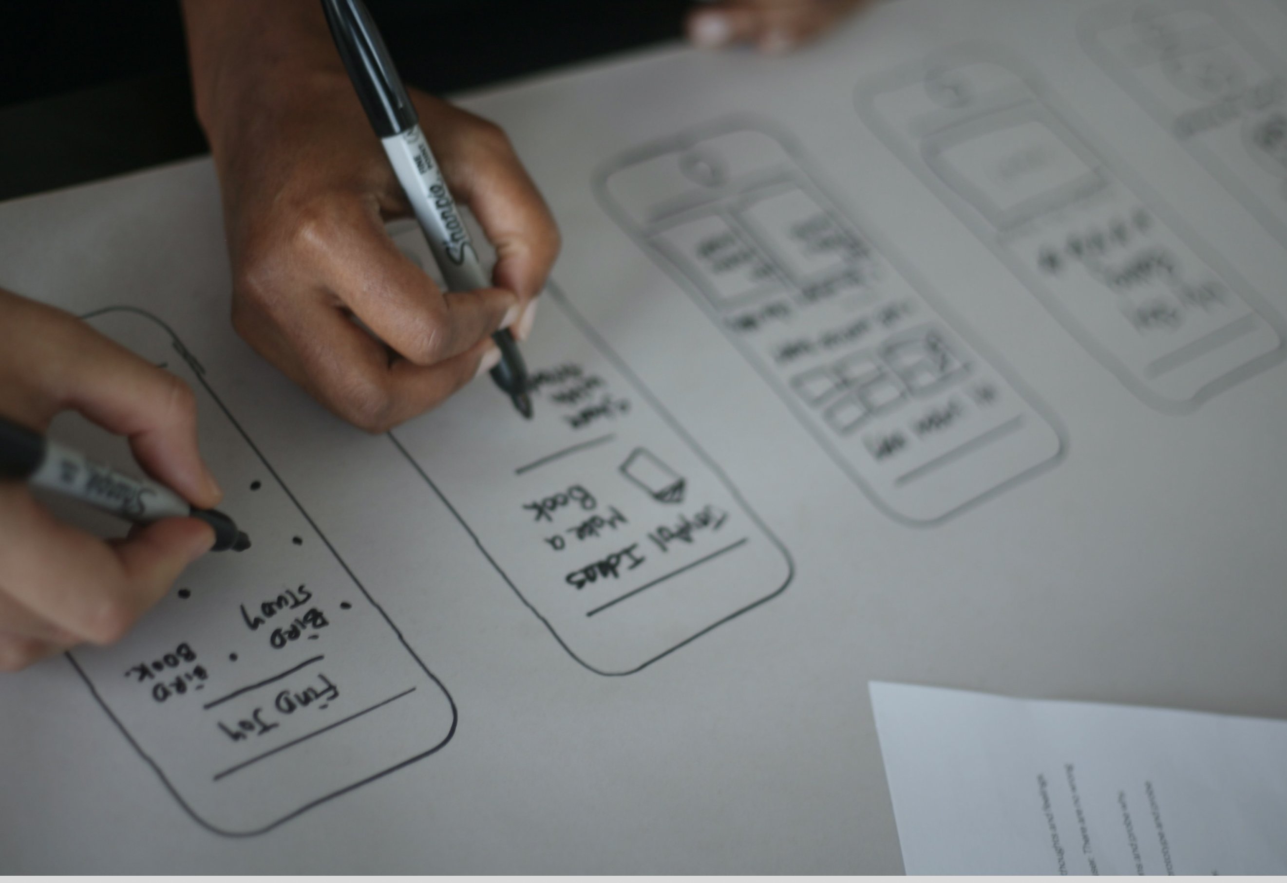 Close up of hands holding sharpies and drawring mobile phone wireframes