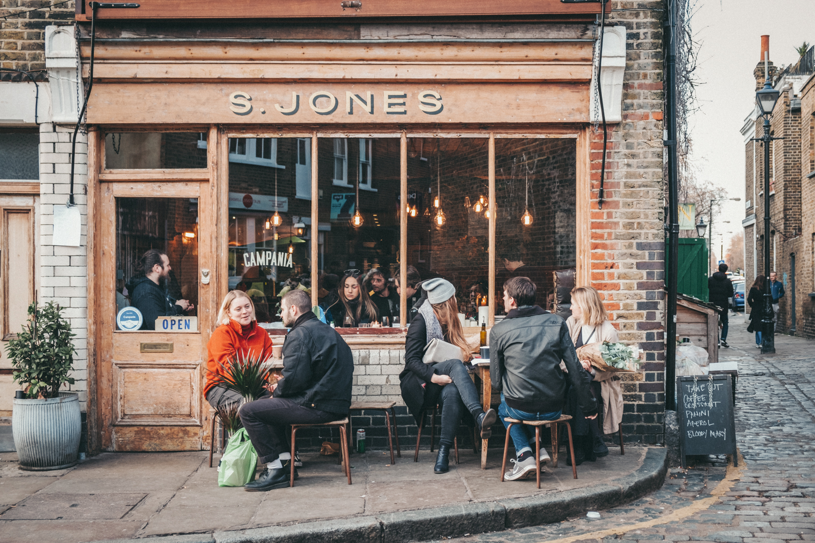 young people eat and drink outside a cafe
