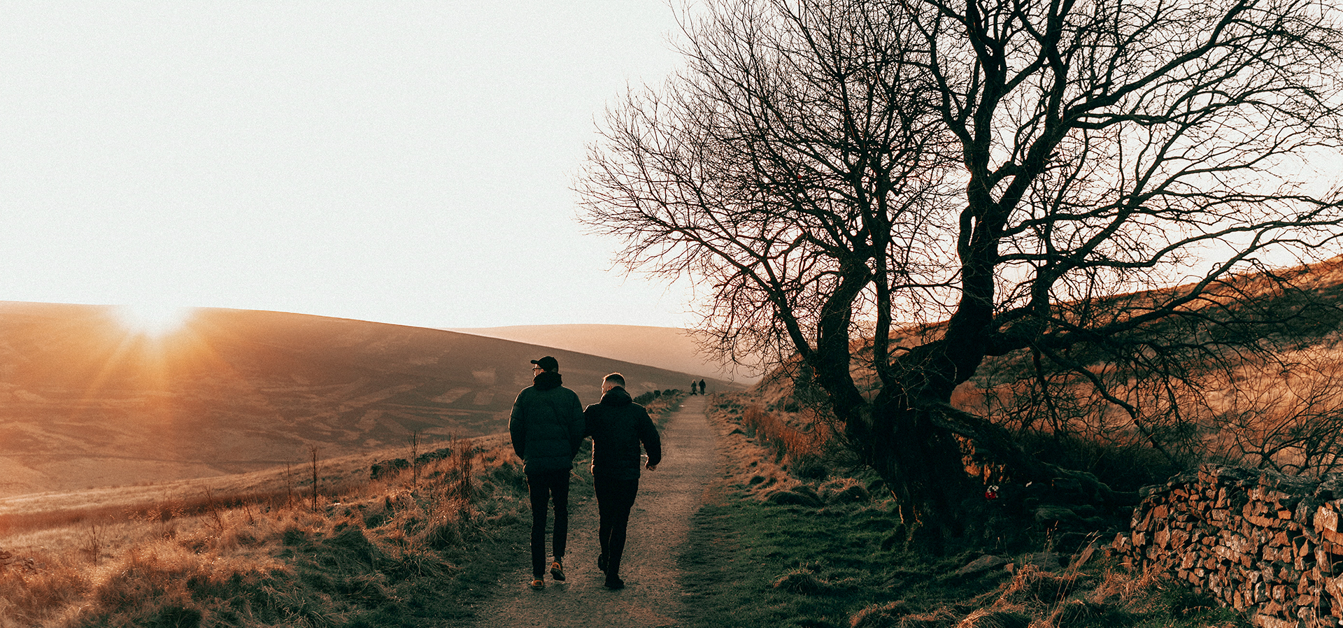 two men walk over a hill in the sunset