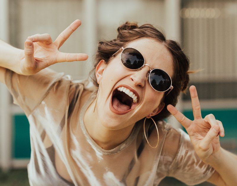 woman holding up peace signs smiling