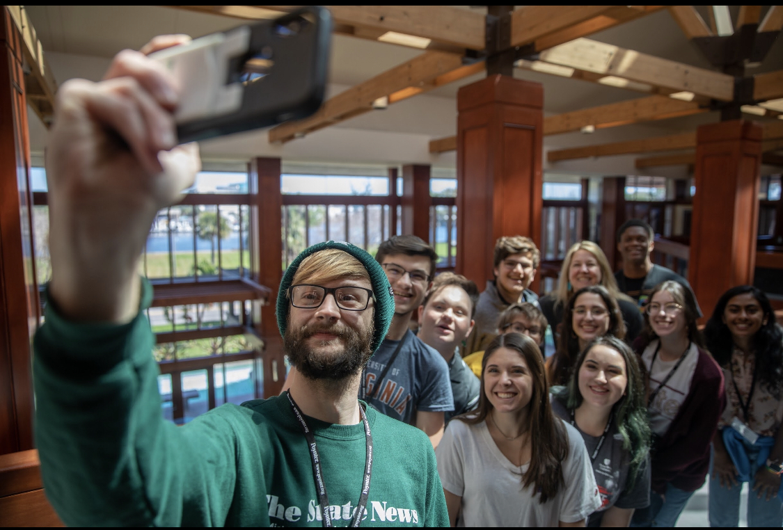 A Poynter Institute representative poses for a selfie with young people. Photo courtesy of Evan Jones.