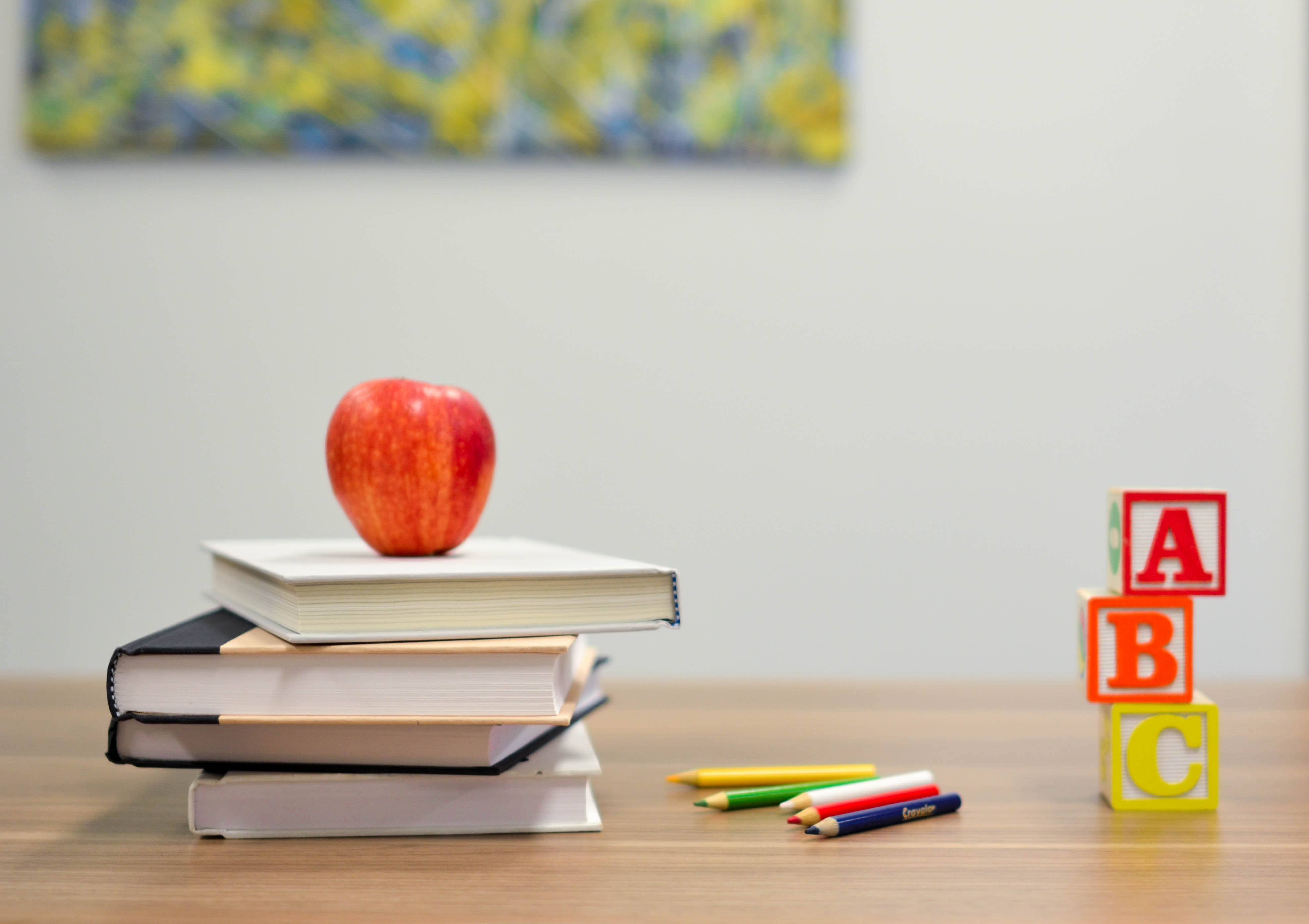 An apple on top of a stack of books rests on a desk with colored pencils and blocks. Courtesy of Element5 Digital on Unsplash.