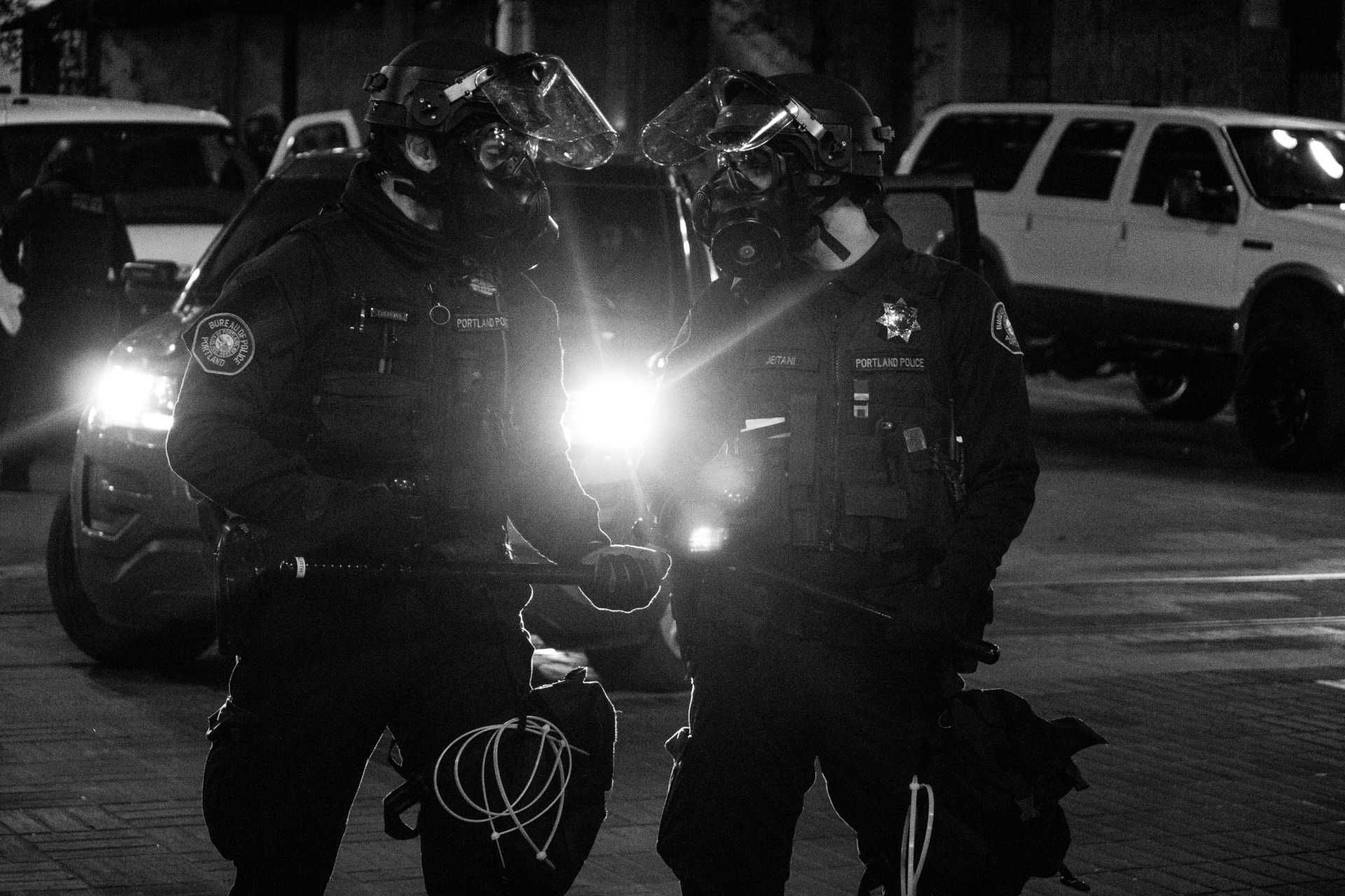 Two police officers in riot gear. Photo courtesy of Tito Texidor !!! on Unsplash.