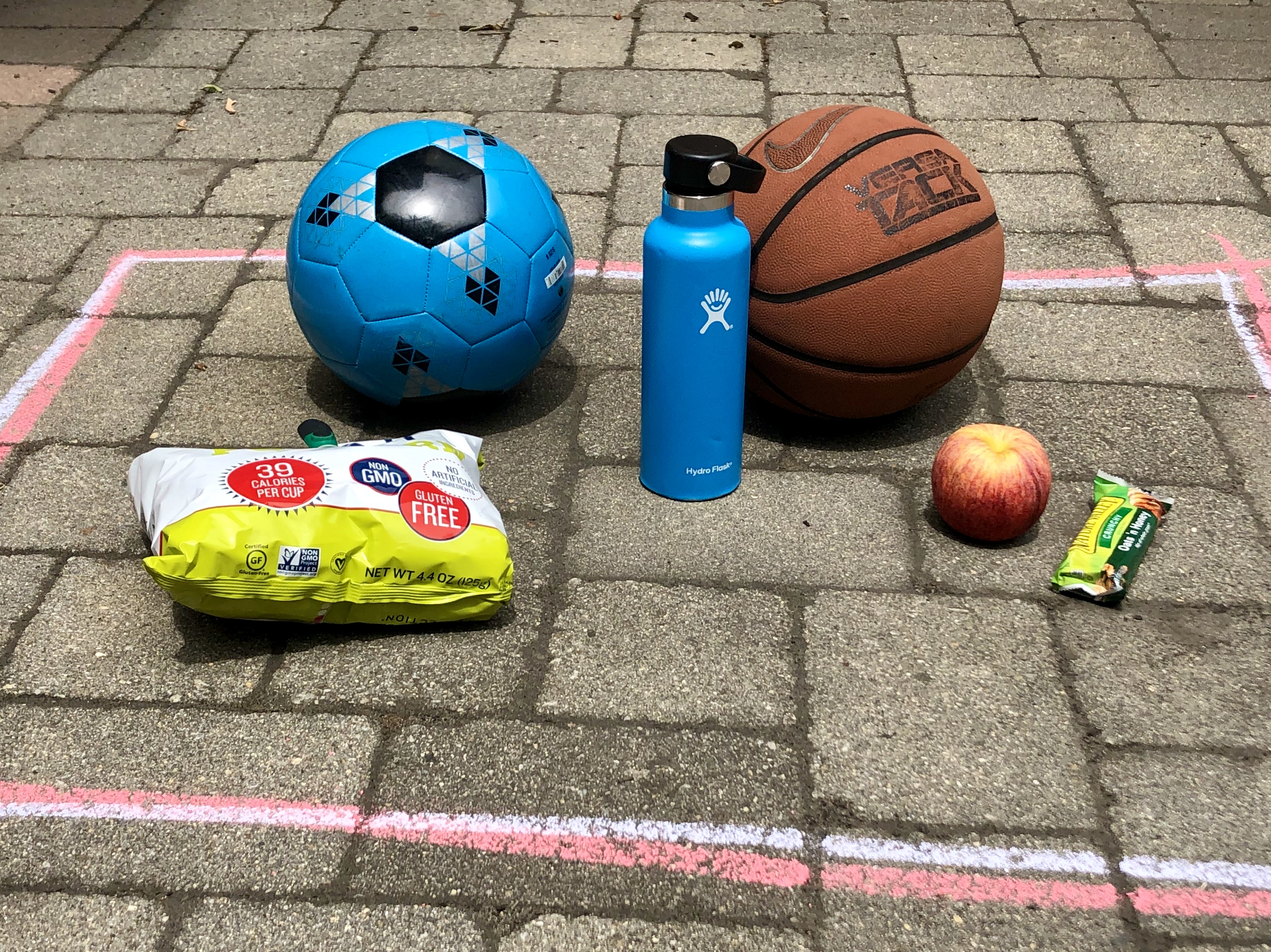 A soccer ball, Hydroflask water bottle, basketball, and various snacks inside a chalk-drawn square. Photo courtesy of Lauren Choy.