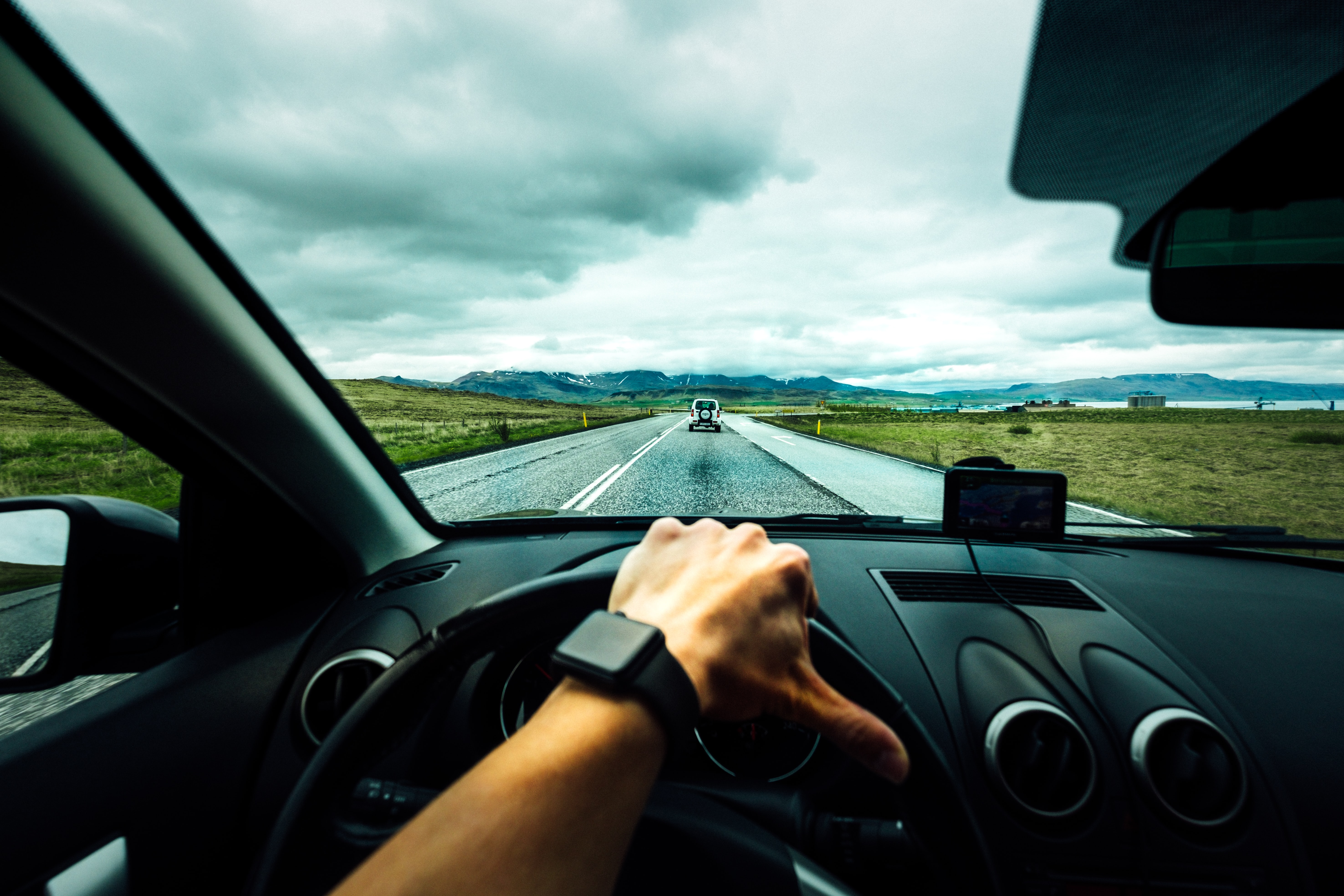 A hand on the steering wheel of a car driving down a long road towards mountains. Courtesy of Tim Foster on Unsplash.