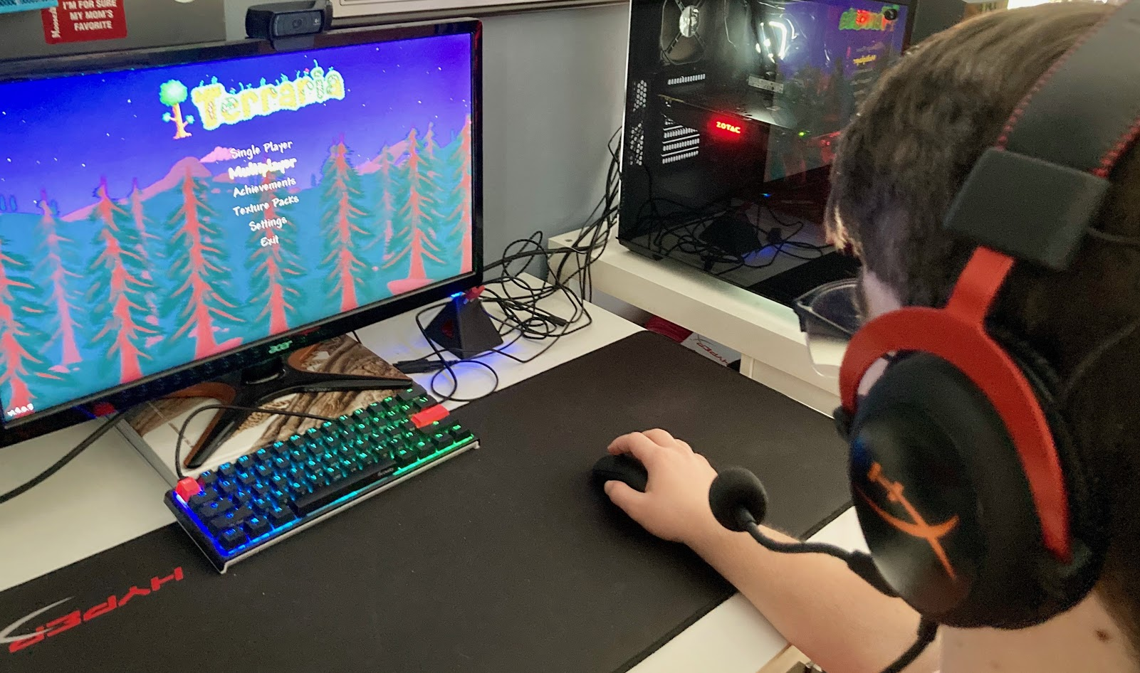"A person wearing headphones plays ""Terraria"" on a desktop computer. Photo courtesy of Emmett Hughes."