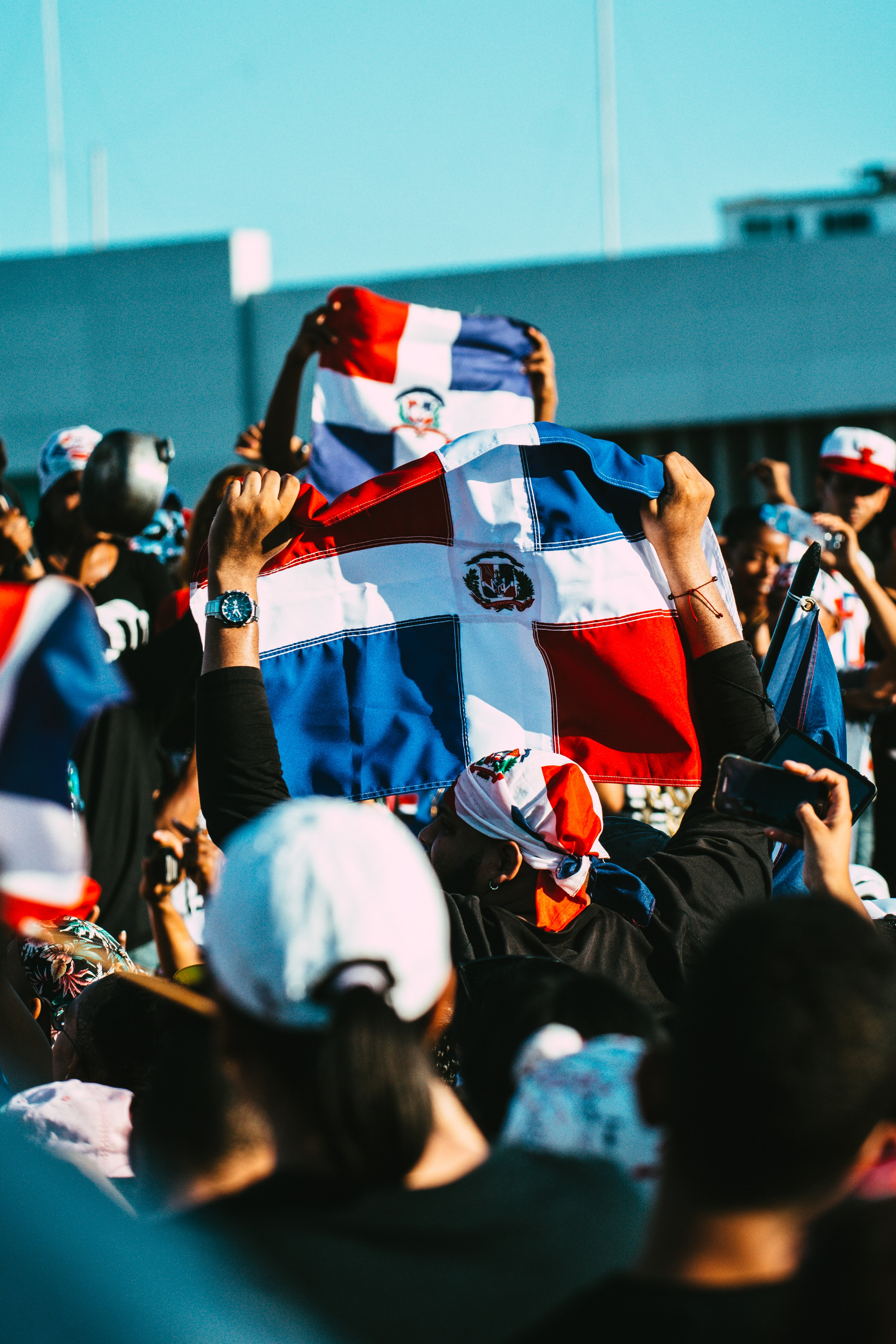 A gathering of people hold Dominican Republic flags in the air. Photo courtesy of Kelvin Moquete on Unsplash.