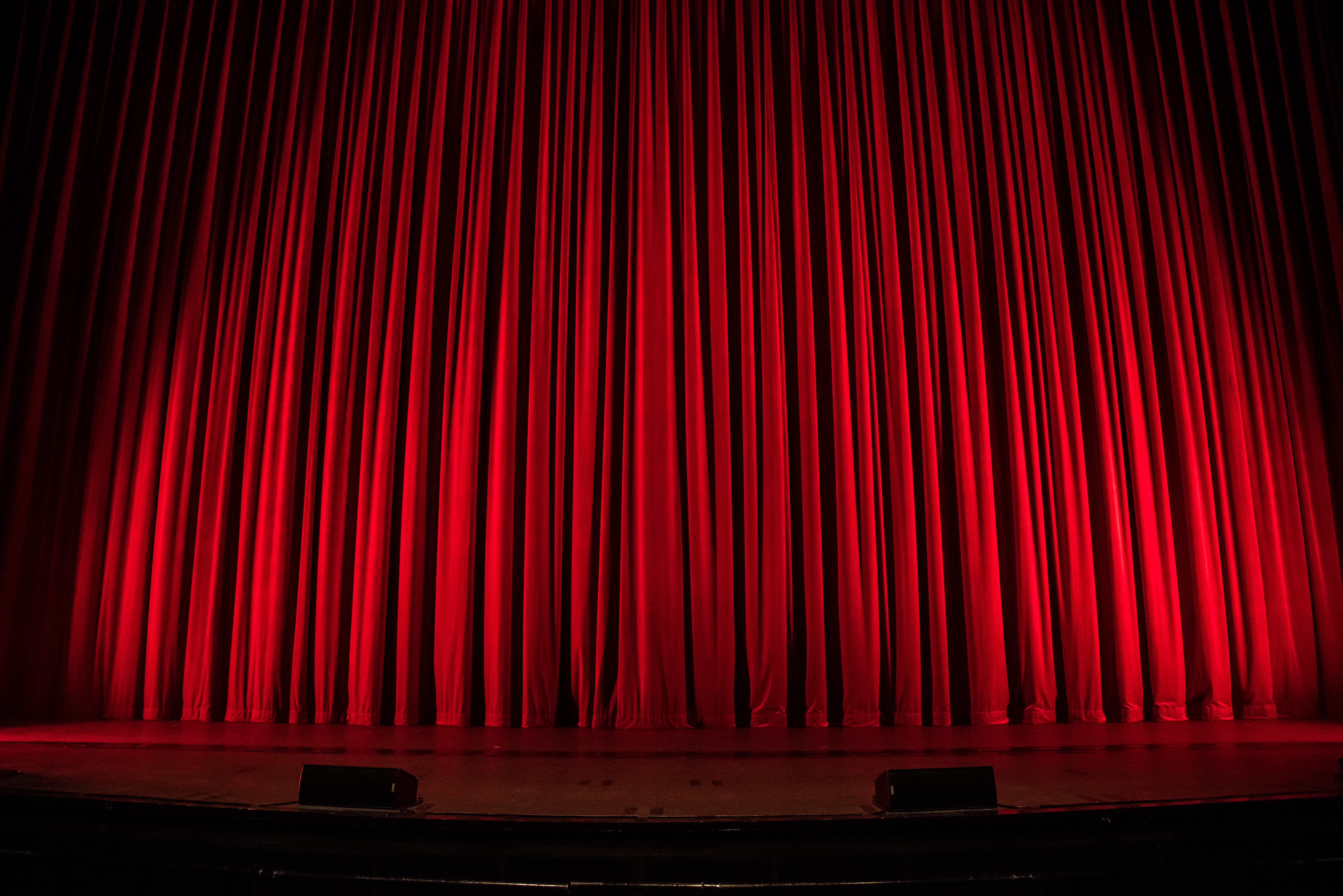 Red curtains drawn on a theatre's stage. Photo courtesy of Rob Laughter on Unsplash.