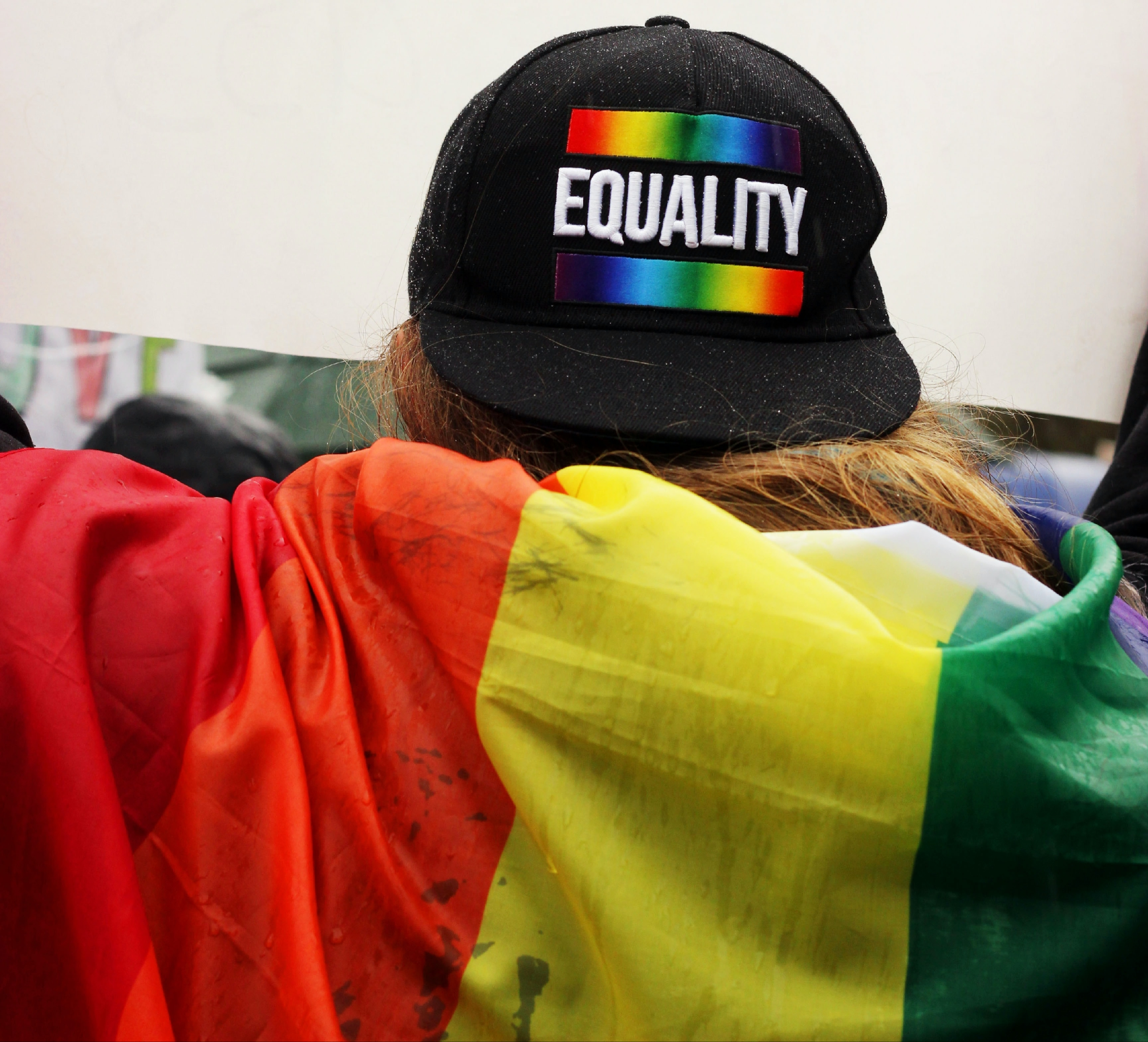 """A person wears a rainbow Pride flag and a backwards cap that reads """"EQUALITY."""""""