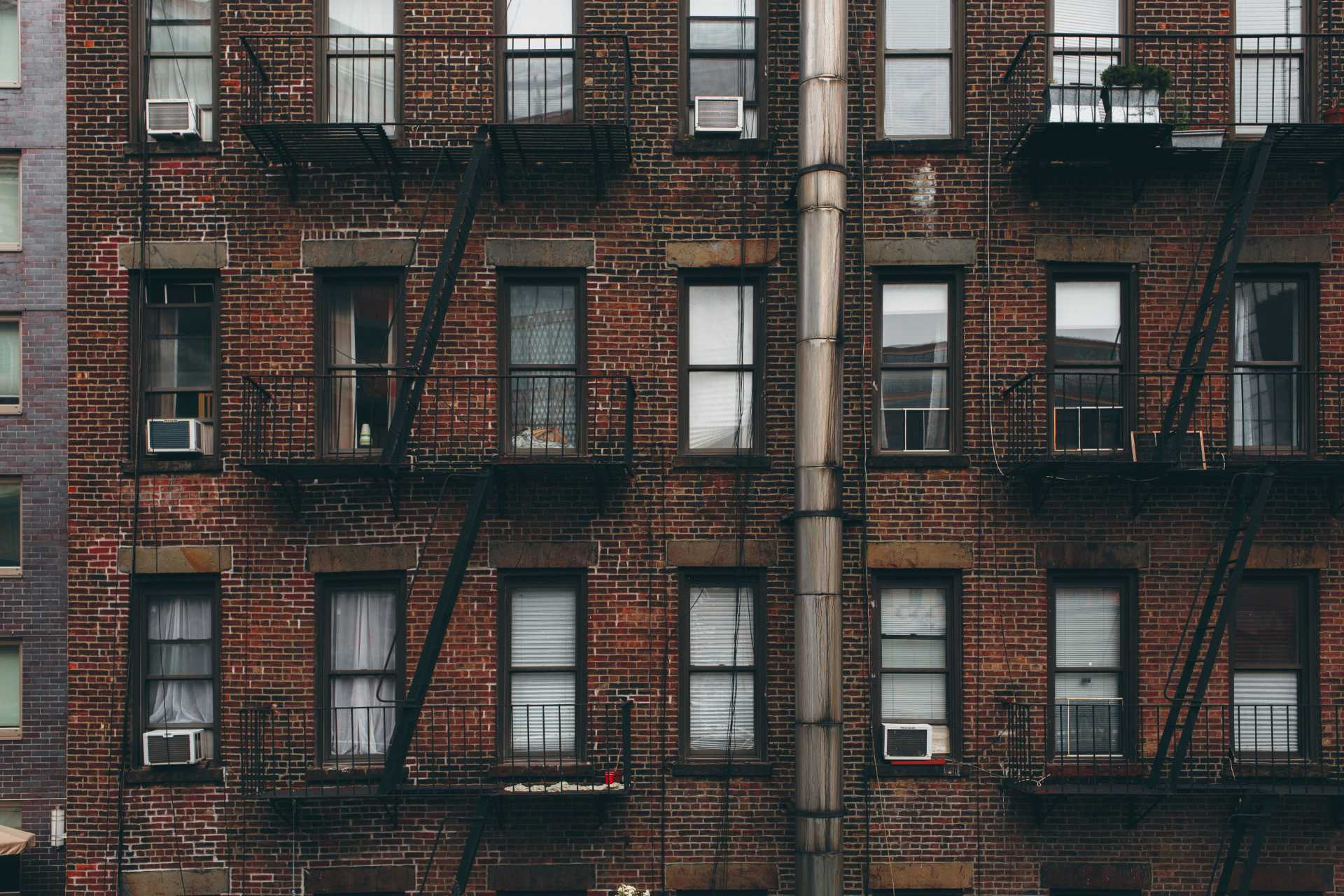 A brick apartment building with fire escapes. Photo courtesy of Anthony Fomin on Unsplash.