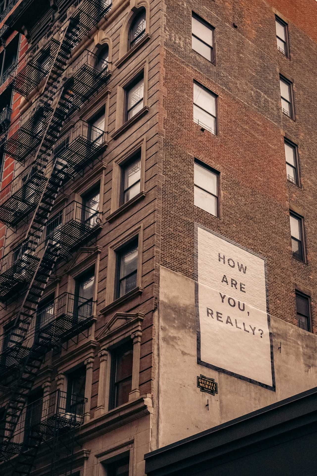 "A sign that says ""How are you, really?"" posted on the side of a brick building. Photo courtesy of Finn on Unsplash."