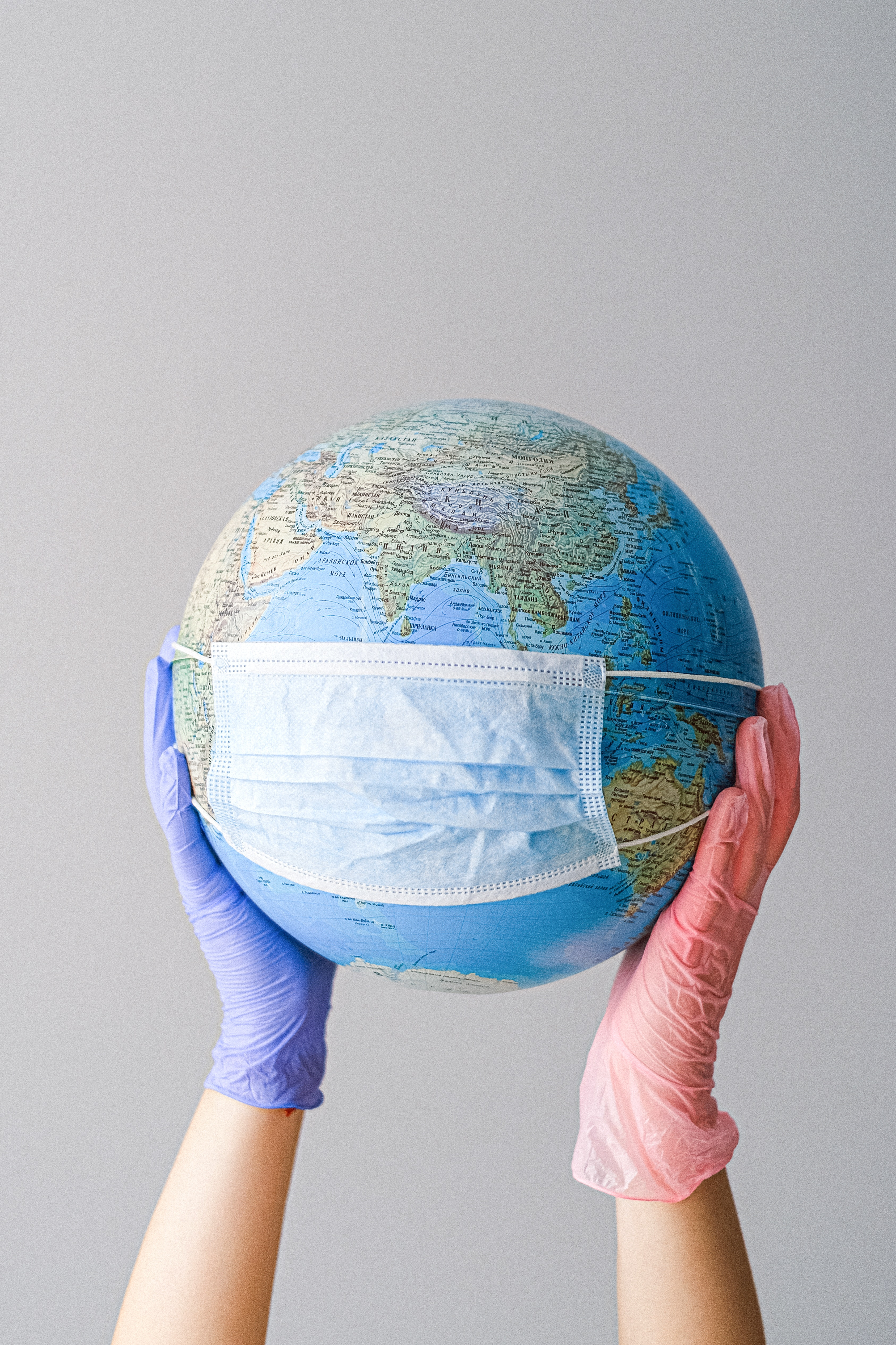 A person wearing latex gloves holds a globe with a disposable surgical face mask on it. Photo courtesy of Anna Shvets from Pexels.
