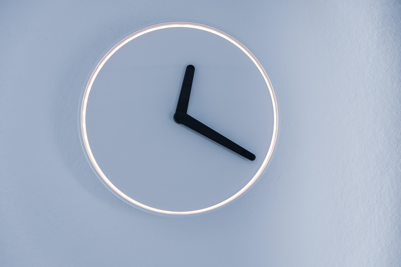 A neon clock with black hands. Photo courtesy of Moritz Kindler on Unsplash.