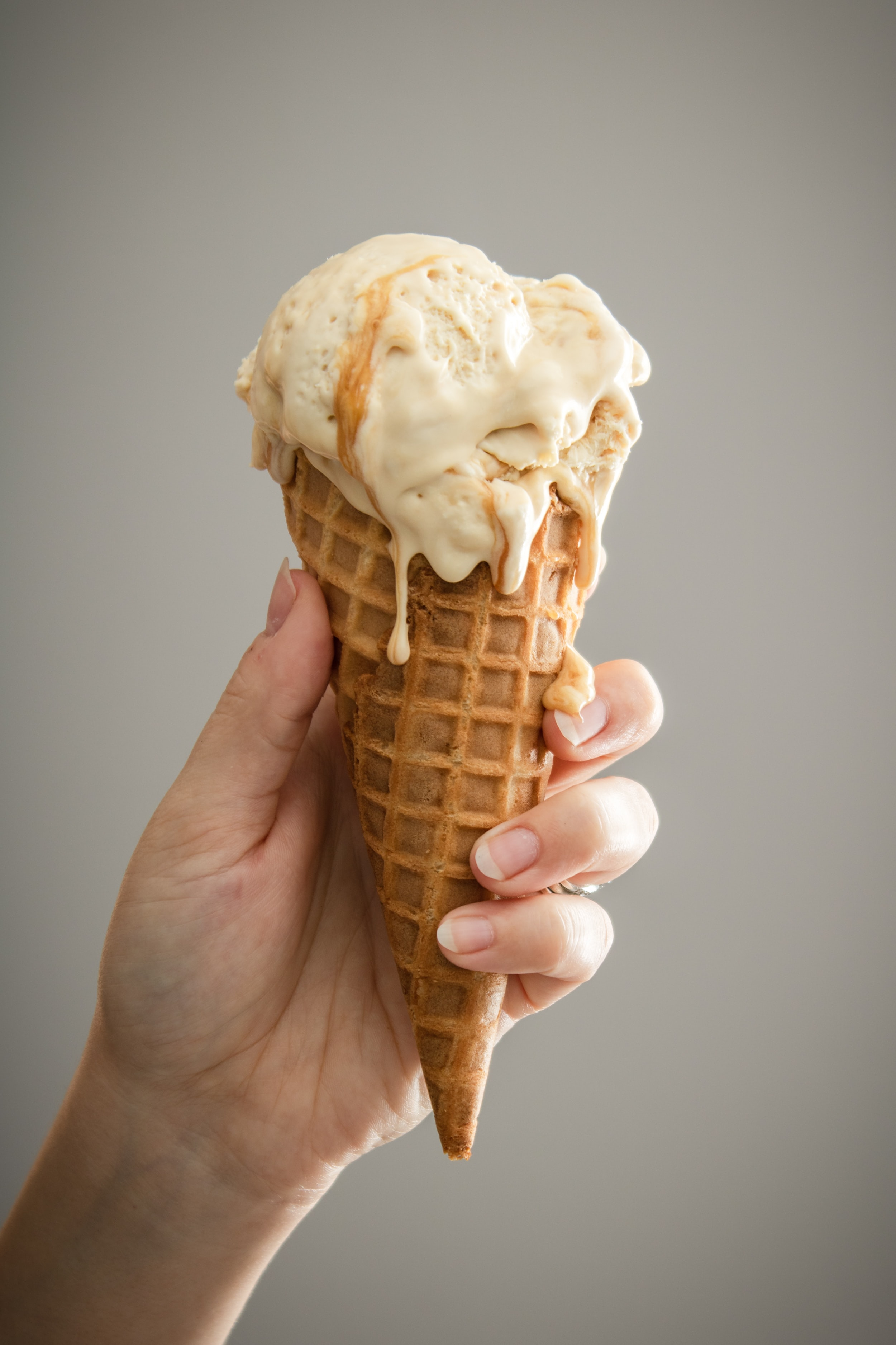 Ice cream melting in hand. Photo courtesy of Dana DeVolk on Unsplash.