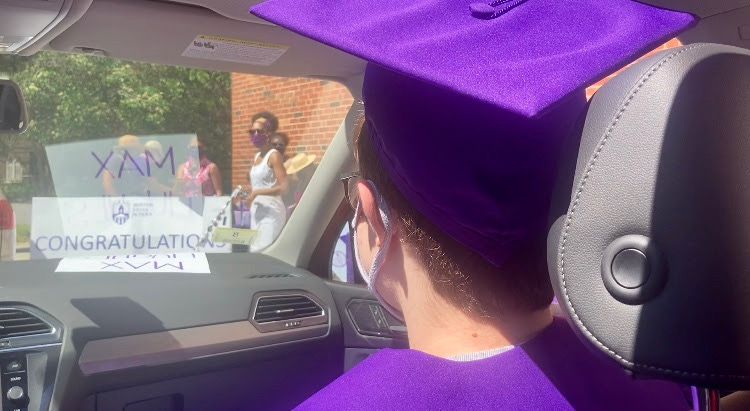 The author wears a purple graduation cap and gown and a mask in a car during a socially-distanced graduation event. Photo courtesy of Maxwell Hughes.
