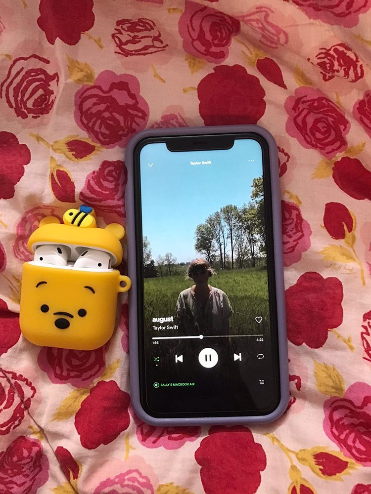 """AirPods in a Winnie the Pooh case next to an iPhone playing """"August"""" by Taylor Swift. Photo courtesy of Sally Phan."""