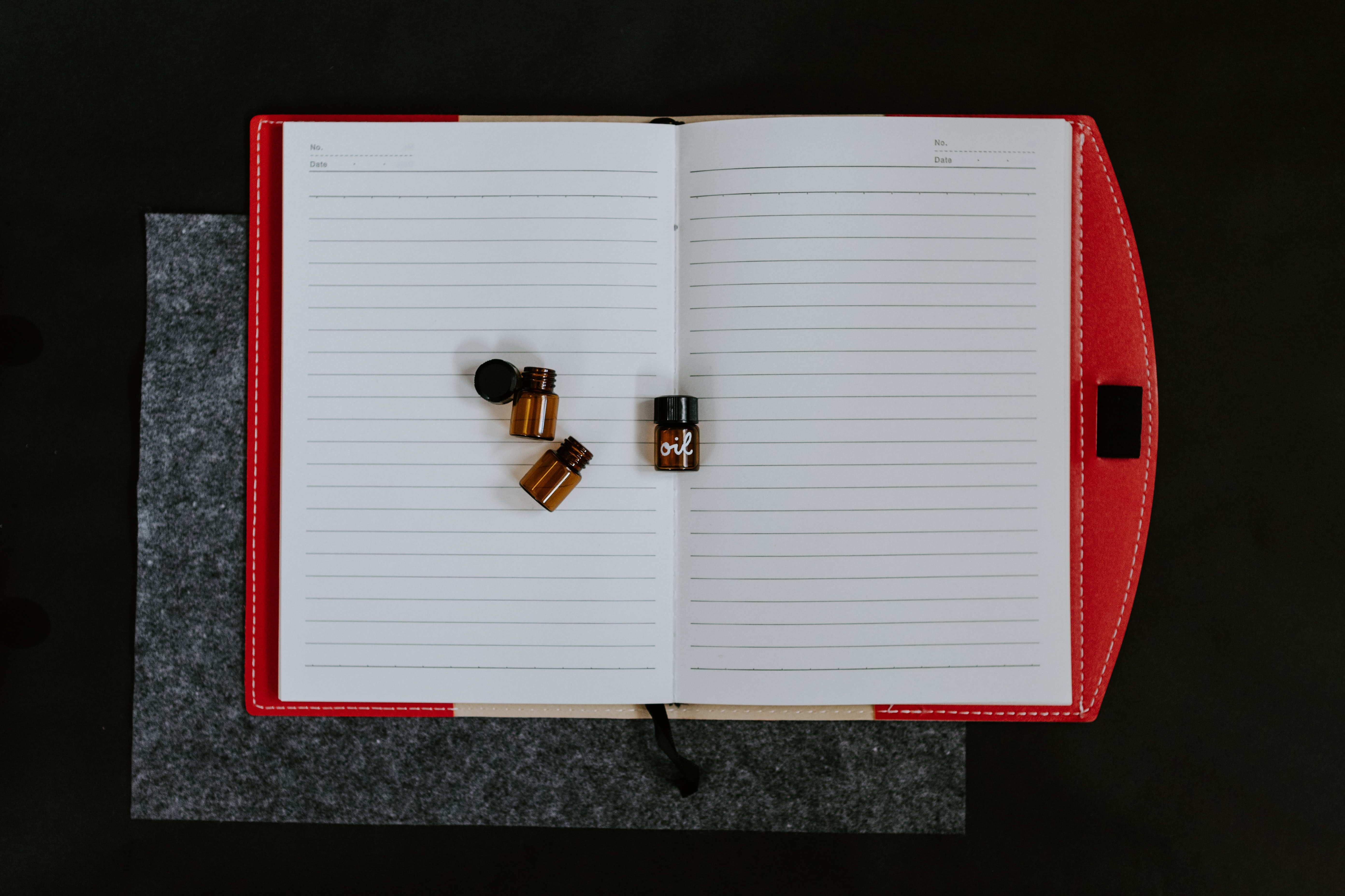 Small jars on top of a notebook with a red cover. Photo courtesy of Kelly Sikkema on Unsplash.