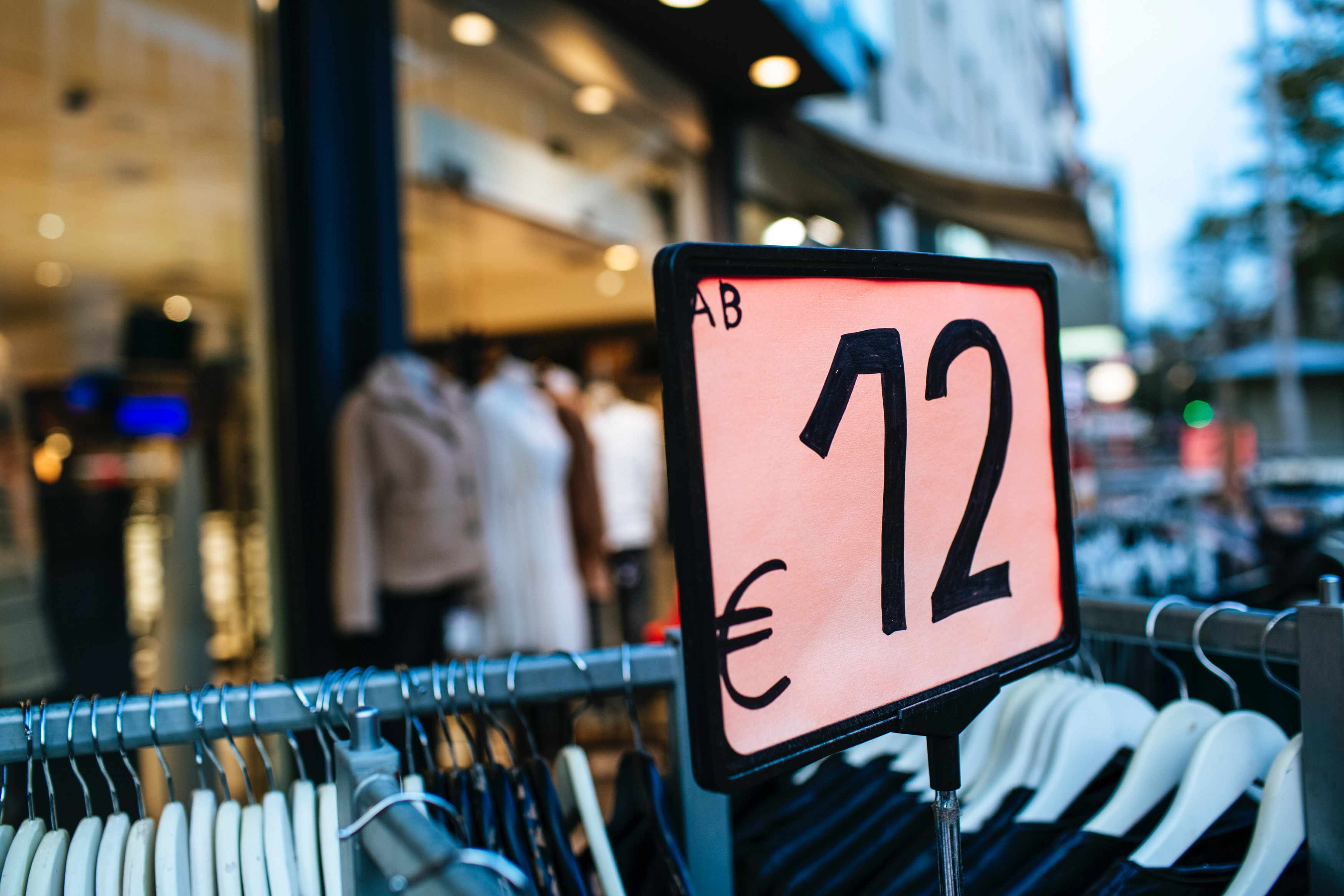 """Racks of clothing stand outside a storefront with a sign that reads """"€12."""" Photo courtesy of Markus Spiske on Unsplash."""