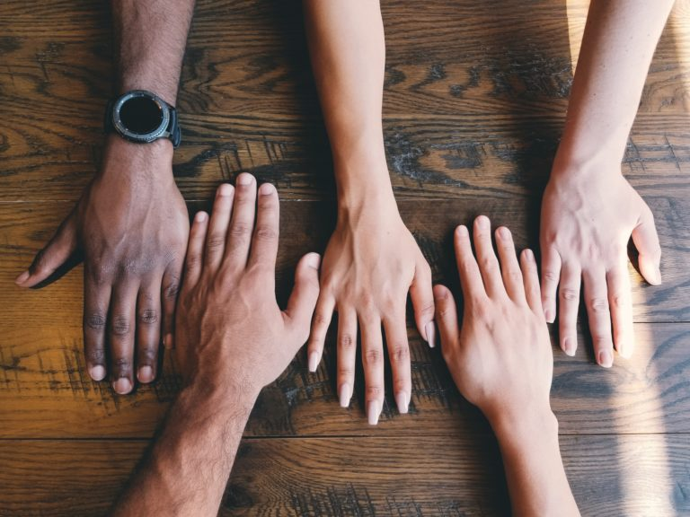 Five human hands on a brown surface. Photo courtesy of Clay Banks on Unsplash.