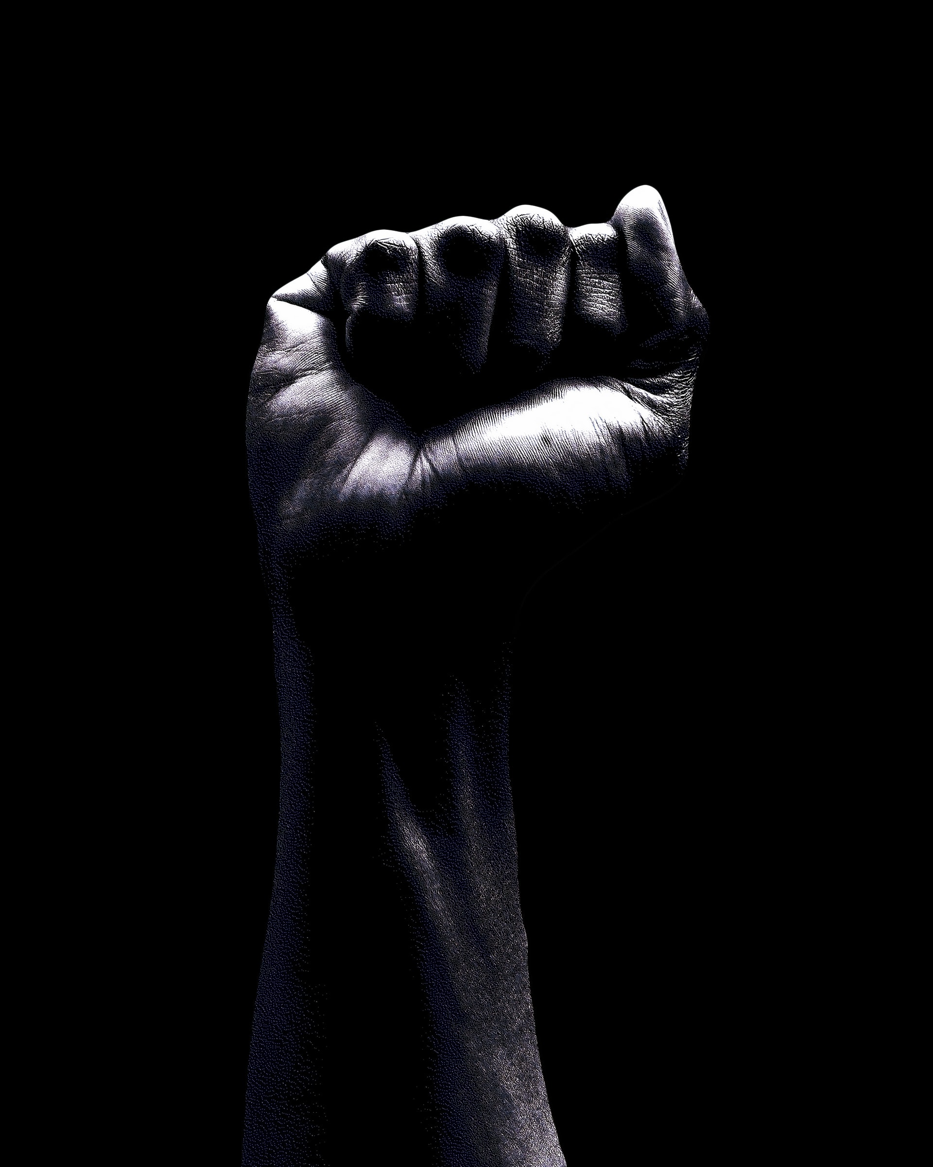 A fist in the air against a black background. Photo courtesy of Oladimeji Odunsi on Unsplash.