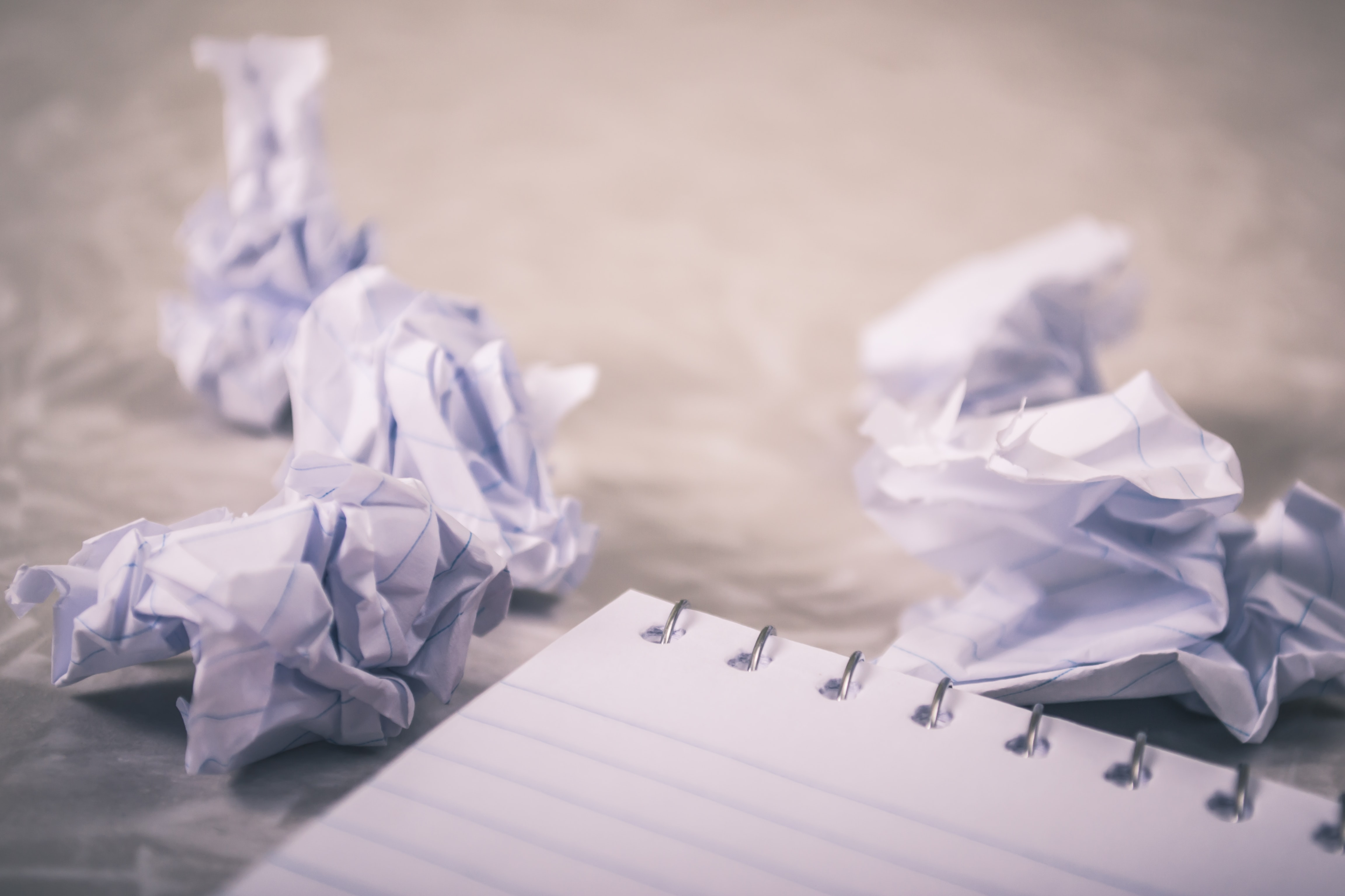 A notebook surrounded by crumpled pieces of paper. Photo courtesy of Steve Johnson on Unsplash.