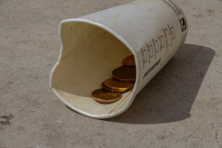 Paper cup filled with coins. Photo courtesy of Nick Fewings via Unsplash.