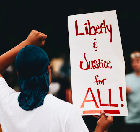 "Protester holding sign saying, ""Liberty and Justice for All."" Photo courtesy of Logan Weaver via Unsplash."