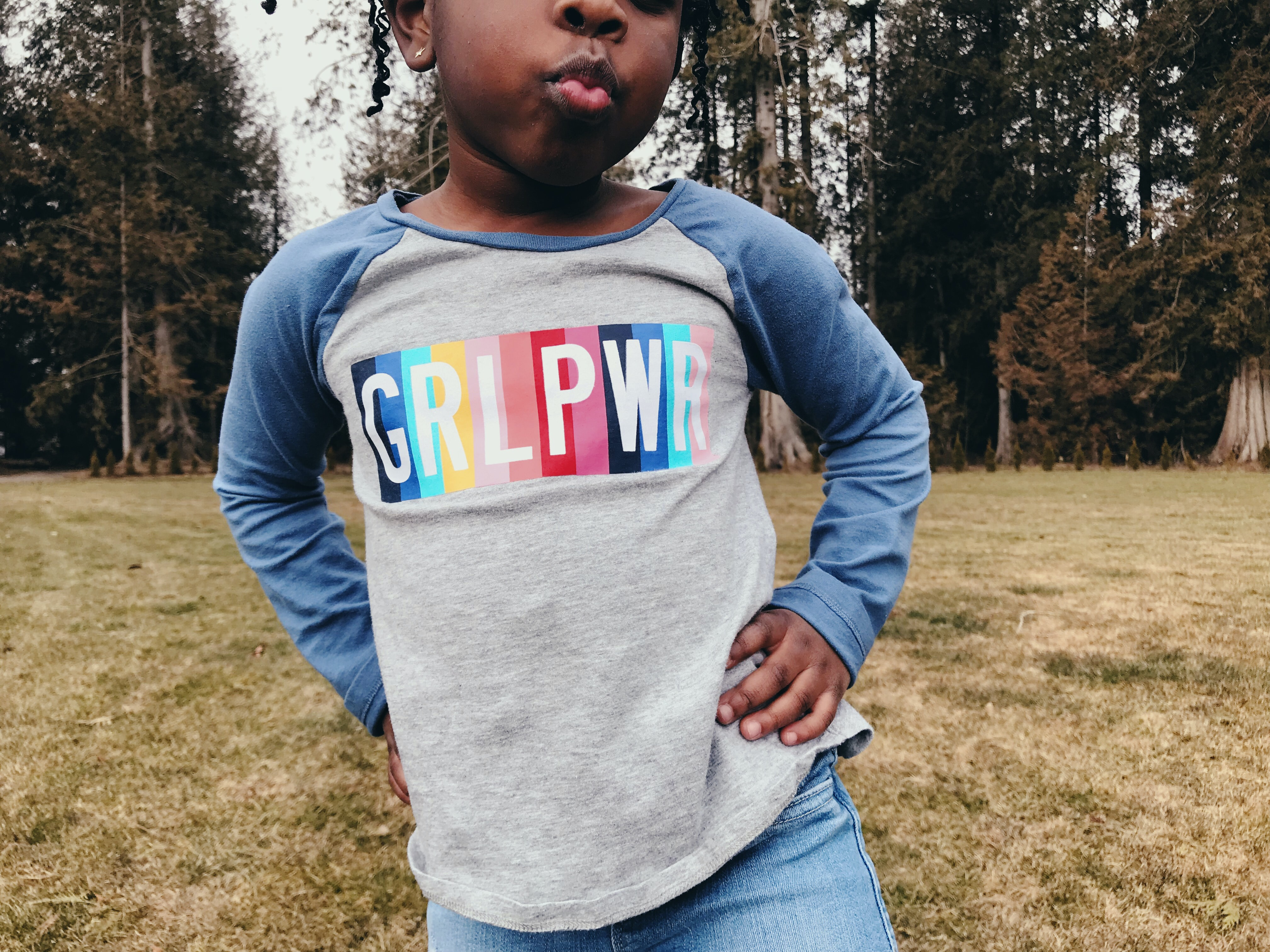 "Young girl wearing a blue ad grey that says ""GRL PWR."" Photo courtesy of Kiana Bosman via Unsplash."