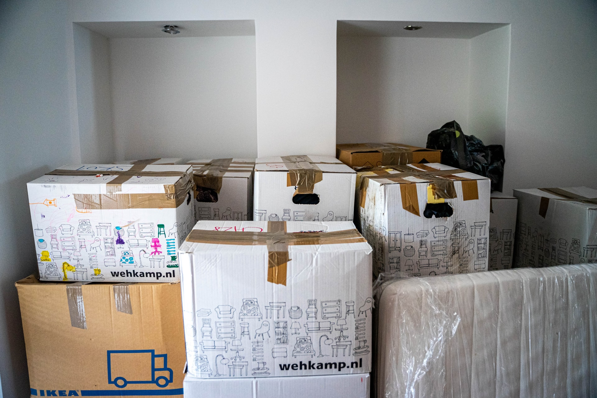Packed, taped, and stacked cardboard boxes. Photo courtesy of Michal Balog on Unsplash.