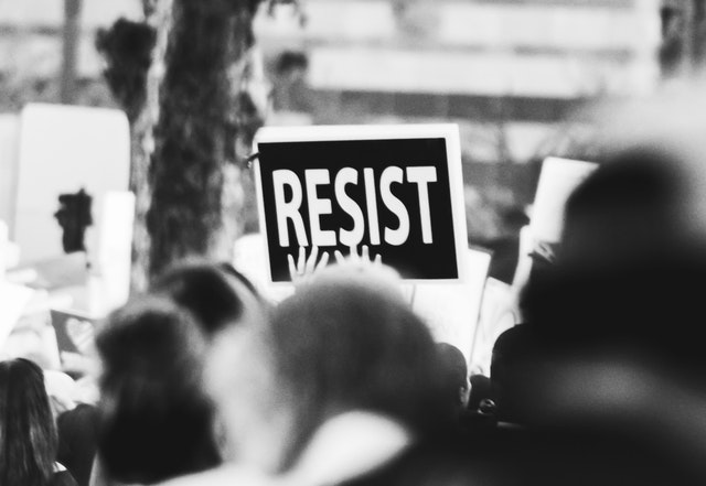 "A black and white sign reading ""Resist."" Photo courtesy of Sides Imagery on Pexels."