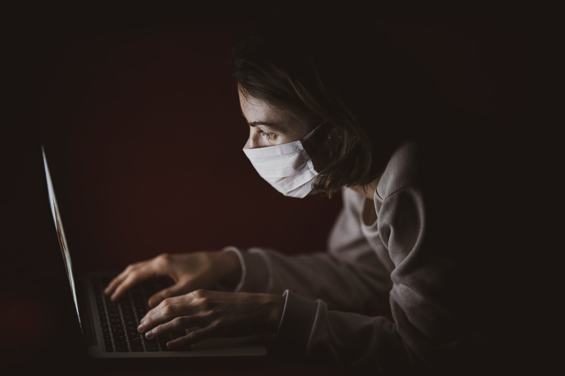 Person using their laptop in the dark with a surgical mask on. Photo courtesy of Egin Akyurt on Unsplash.