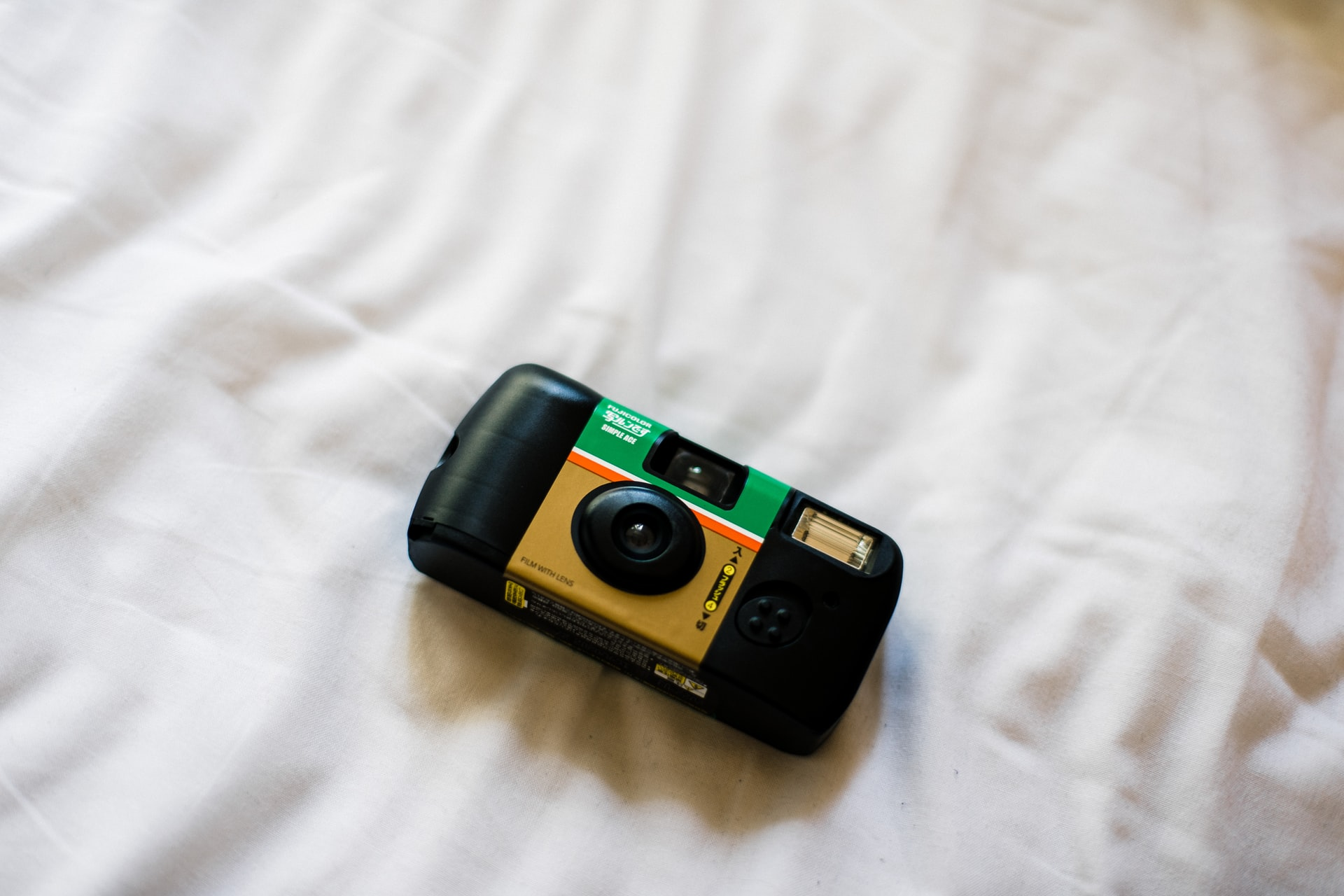 Disposable camera on top of a white sheet. Photo courtesy of Bady Abbas on Unsplash.