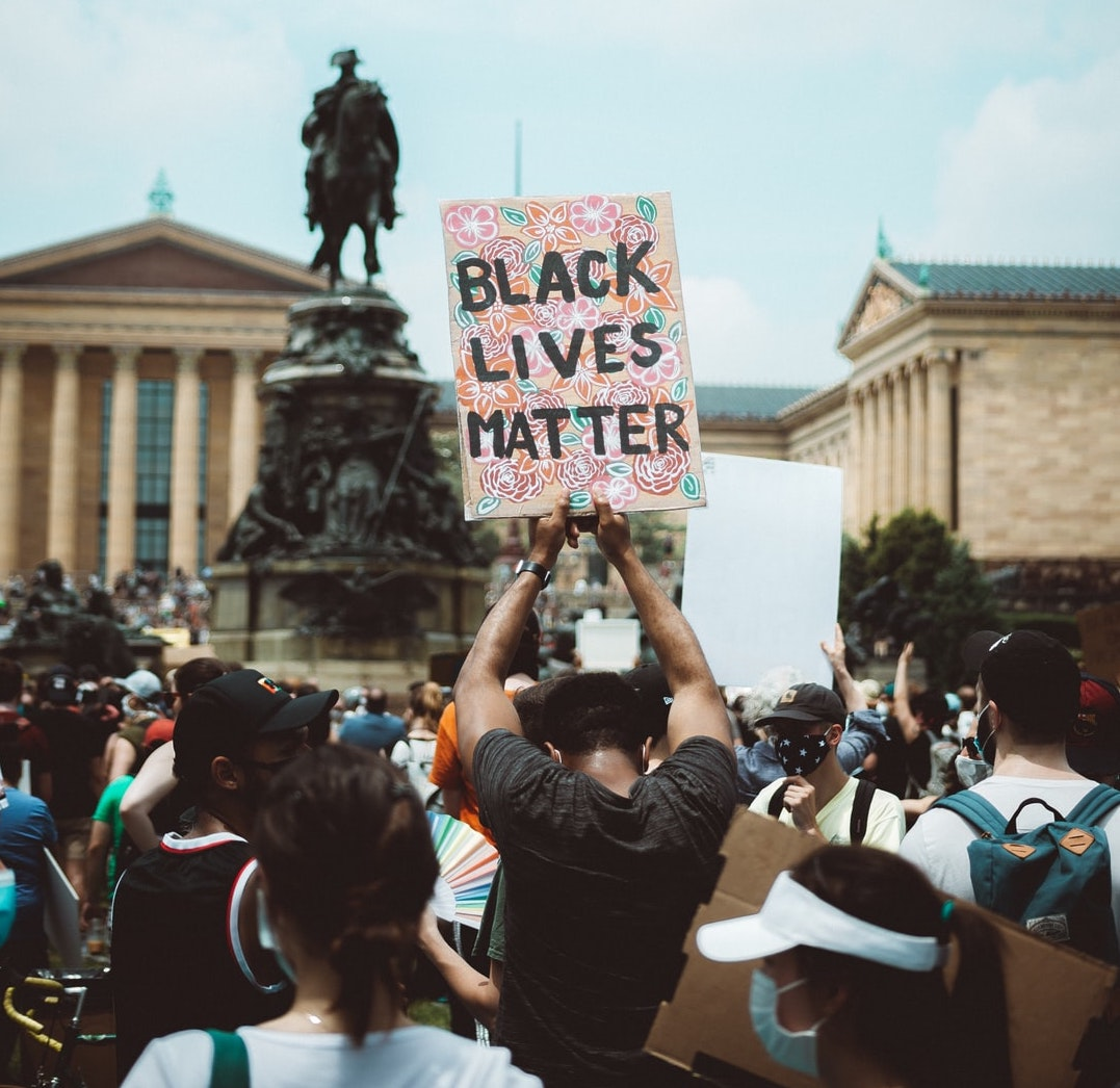 "A protester holds a sign that reads ""Black Lives Matter."" Photo courtesy of Chris Henry on Unsplash."
