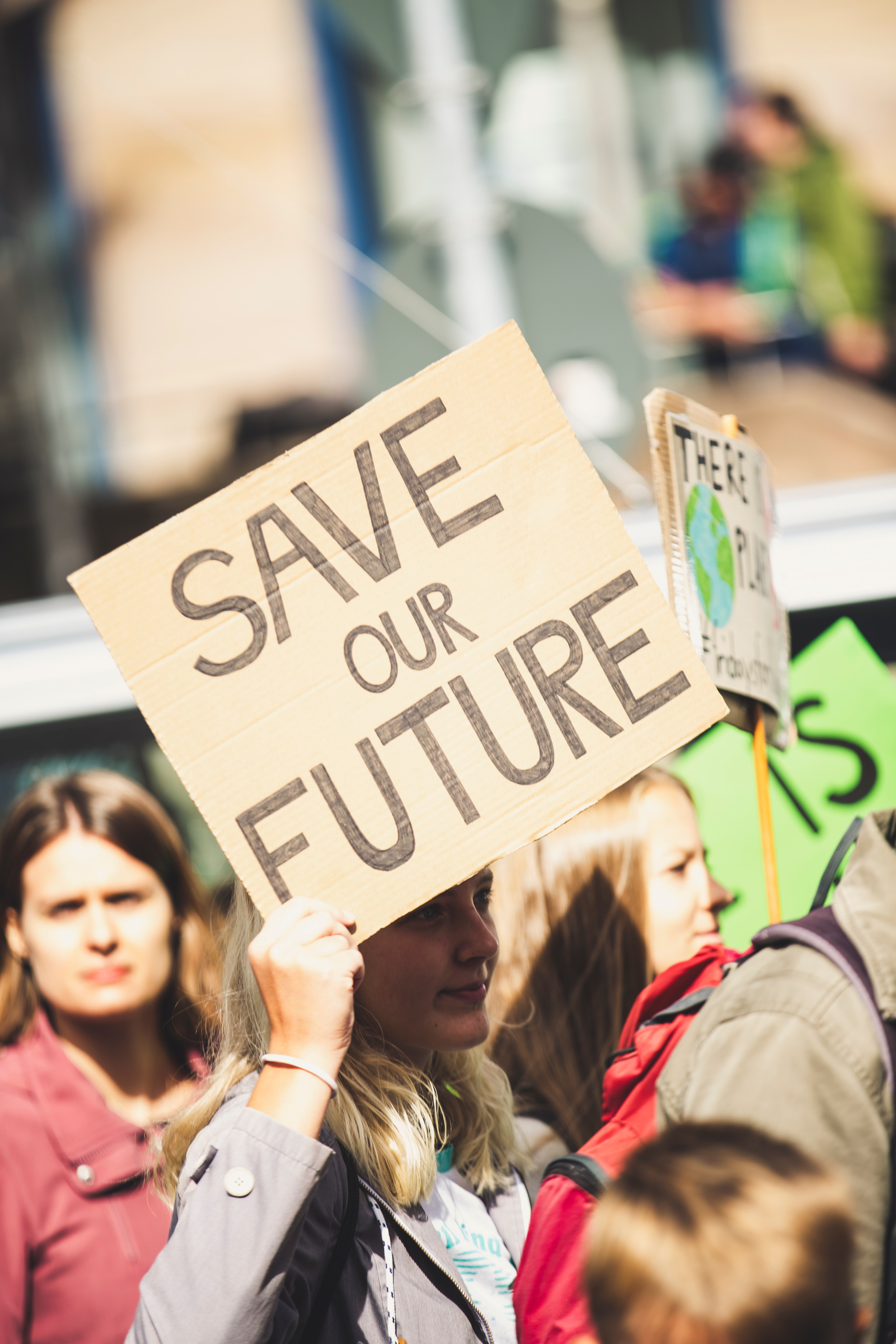 "A photo of someone at a protest holding a sign that says ""Save Our Future."" Photo courtesy Markus Spiske on Unsplash."
