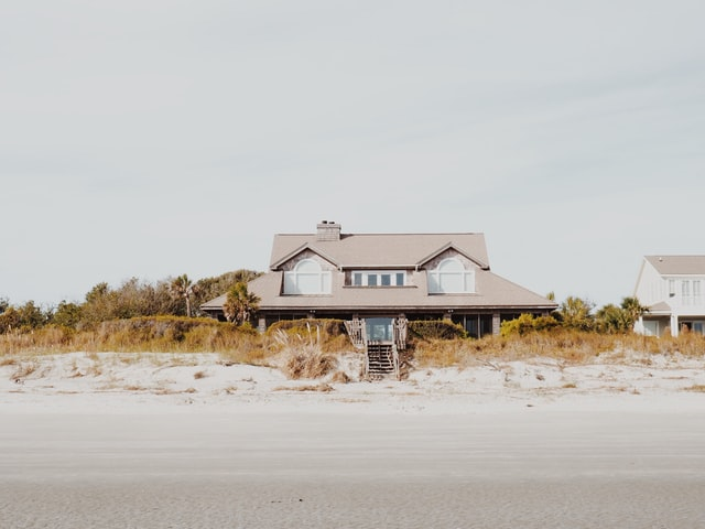 Beach house surrounded by trees. Photo courtesy of Katie Manning on Unsplash.