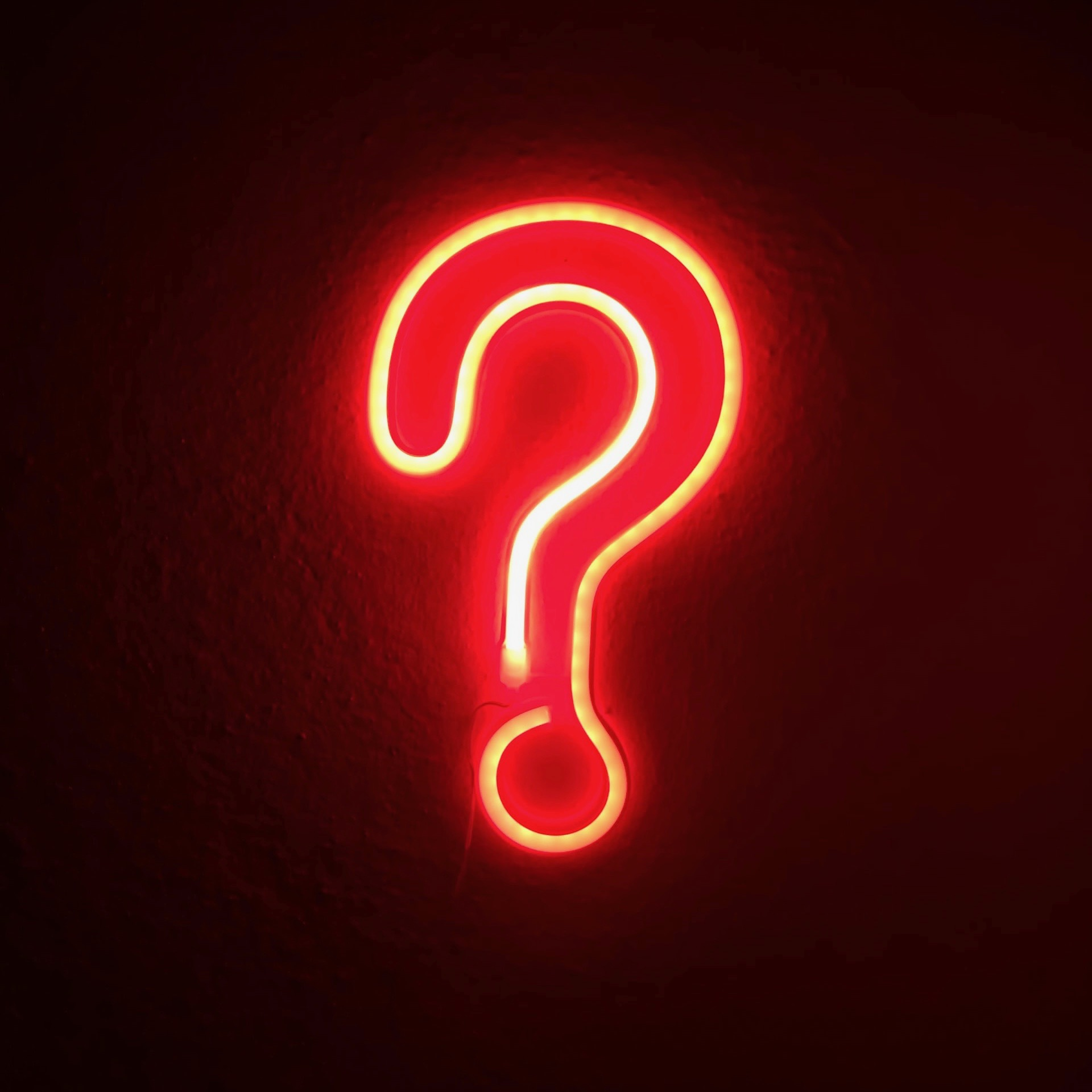 A neon red question mark. Photo courtesy of Simone Secci on Unsplash.