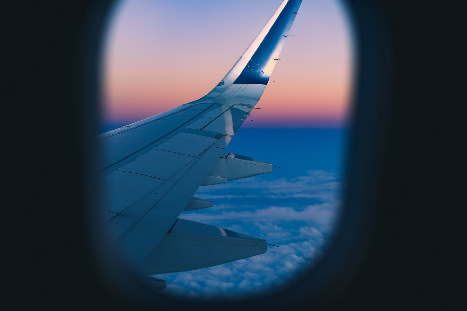 View from an airplane window at sunrise of the plane's wing. Photo courtesy of Dan Gold on Unsplash.