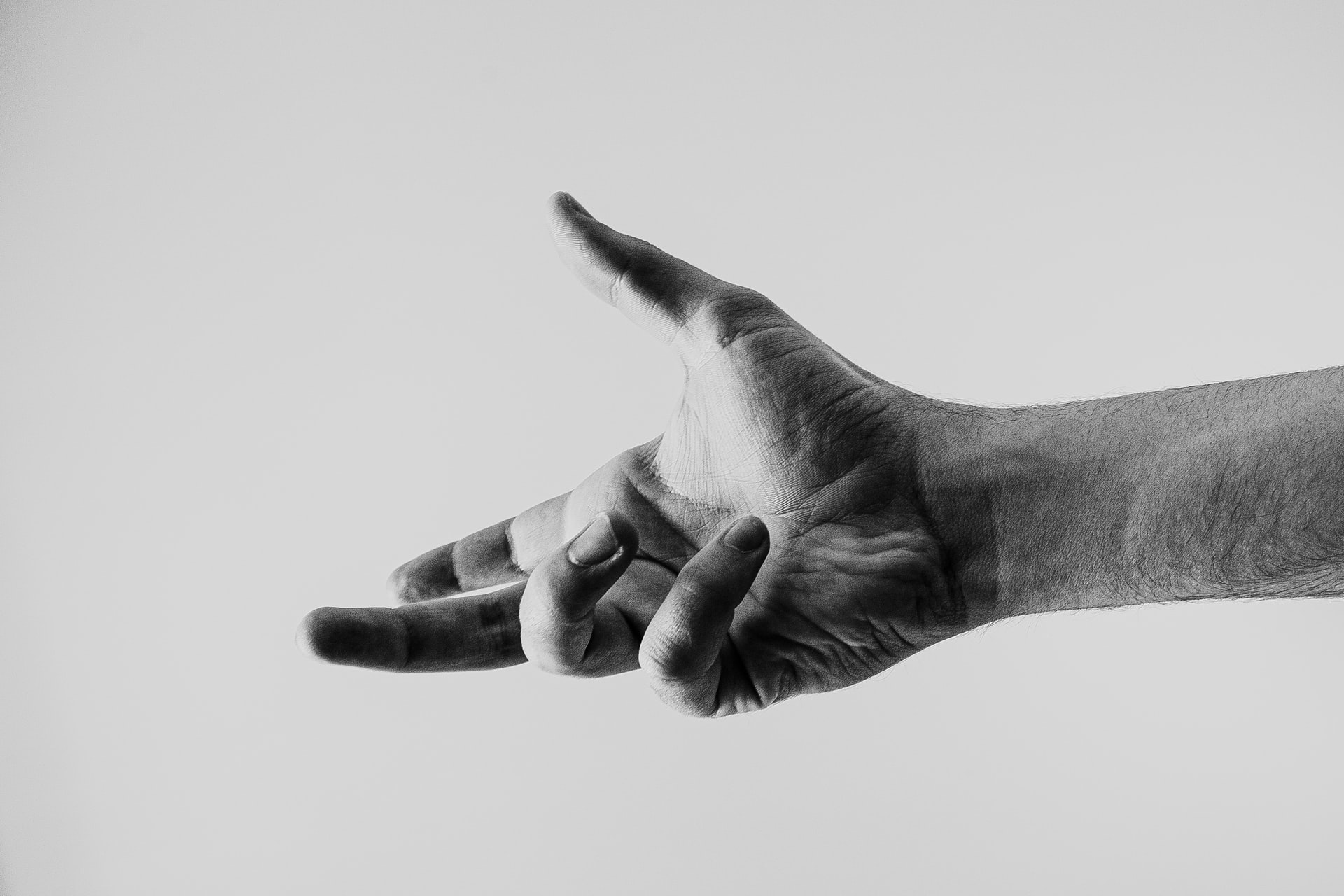 A black and white photo of an outstretched hand. Photo courtesy of Ave Calvar on Unsplash.