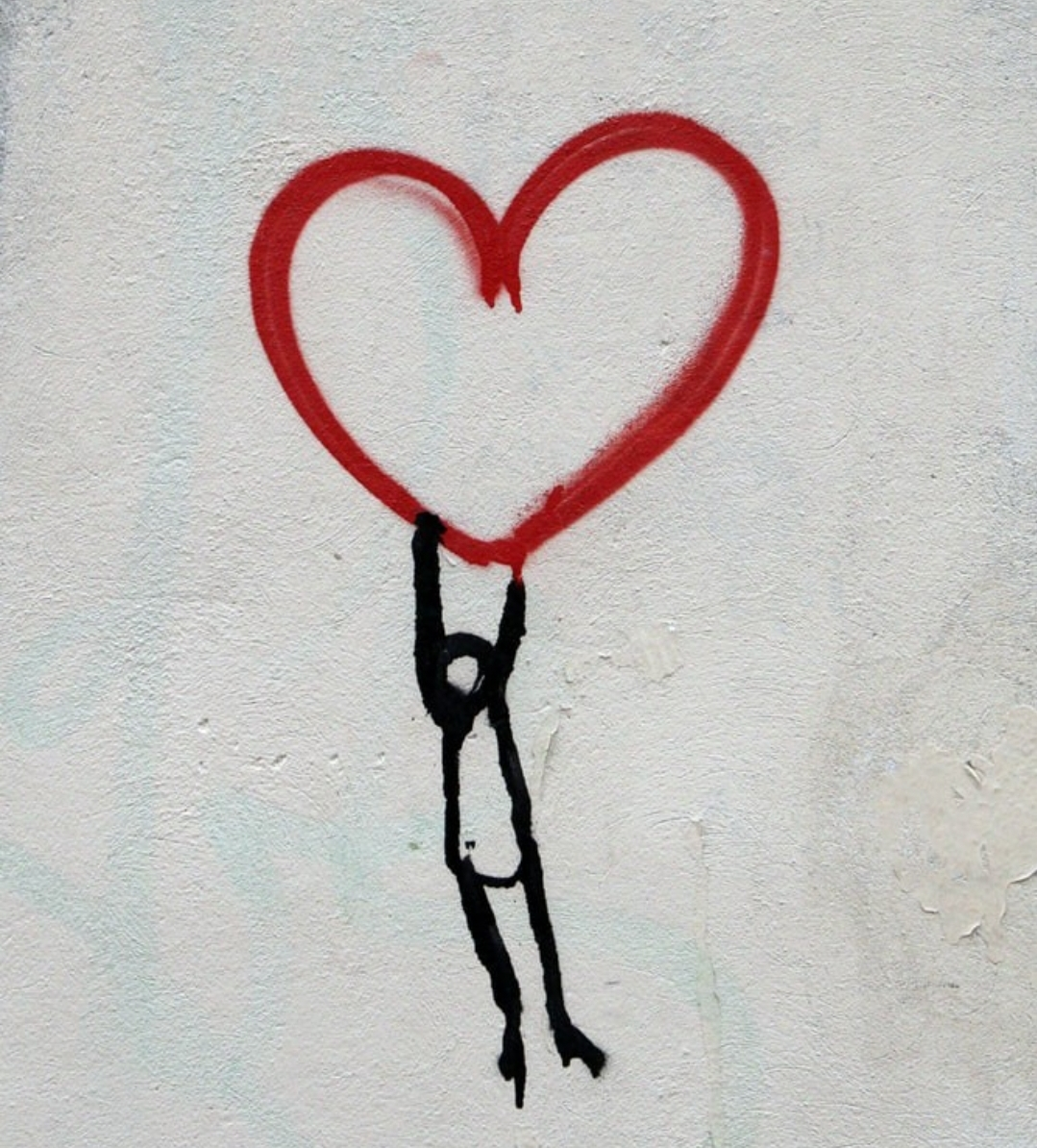 A black stick figure holds a red heart above its head. Photo courtesy of Stacie Bruillant.