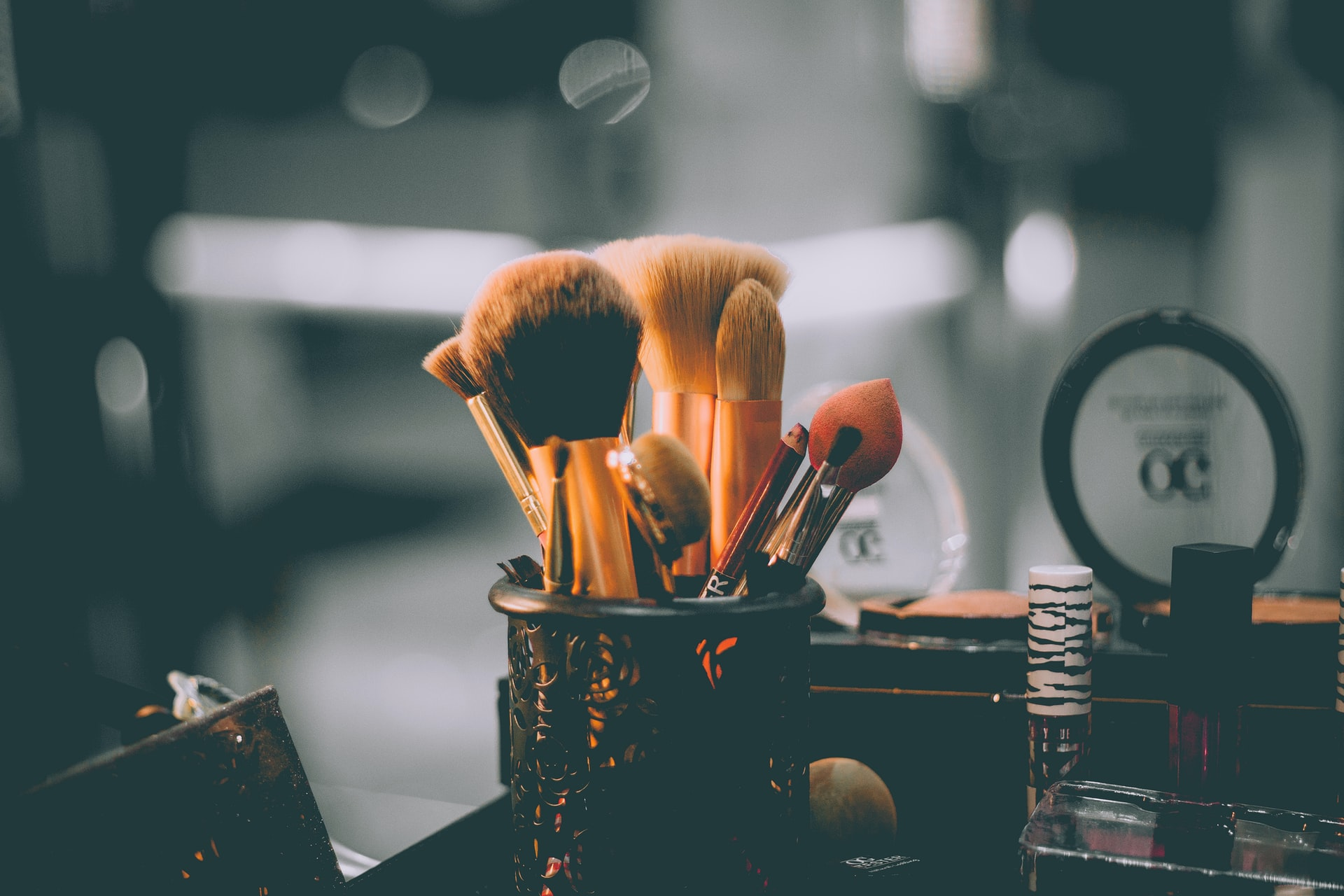 Assorted makeup brushes and makeup on a table. Photo courtesy of Raphael Lovaski on Unsplash.