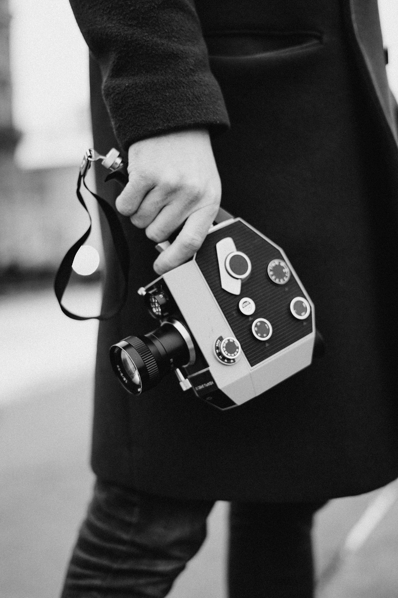 Grayscale photo of a person holding an analog camera. Photo courtesy of Cottonbro on Pexels.