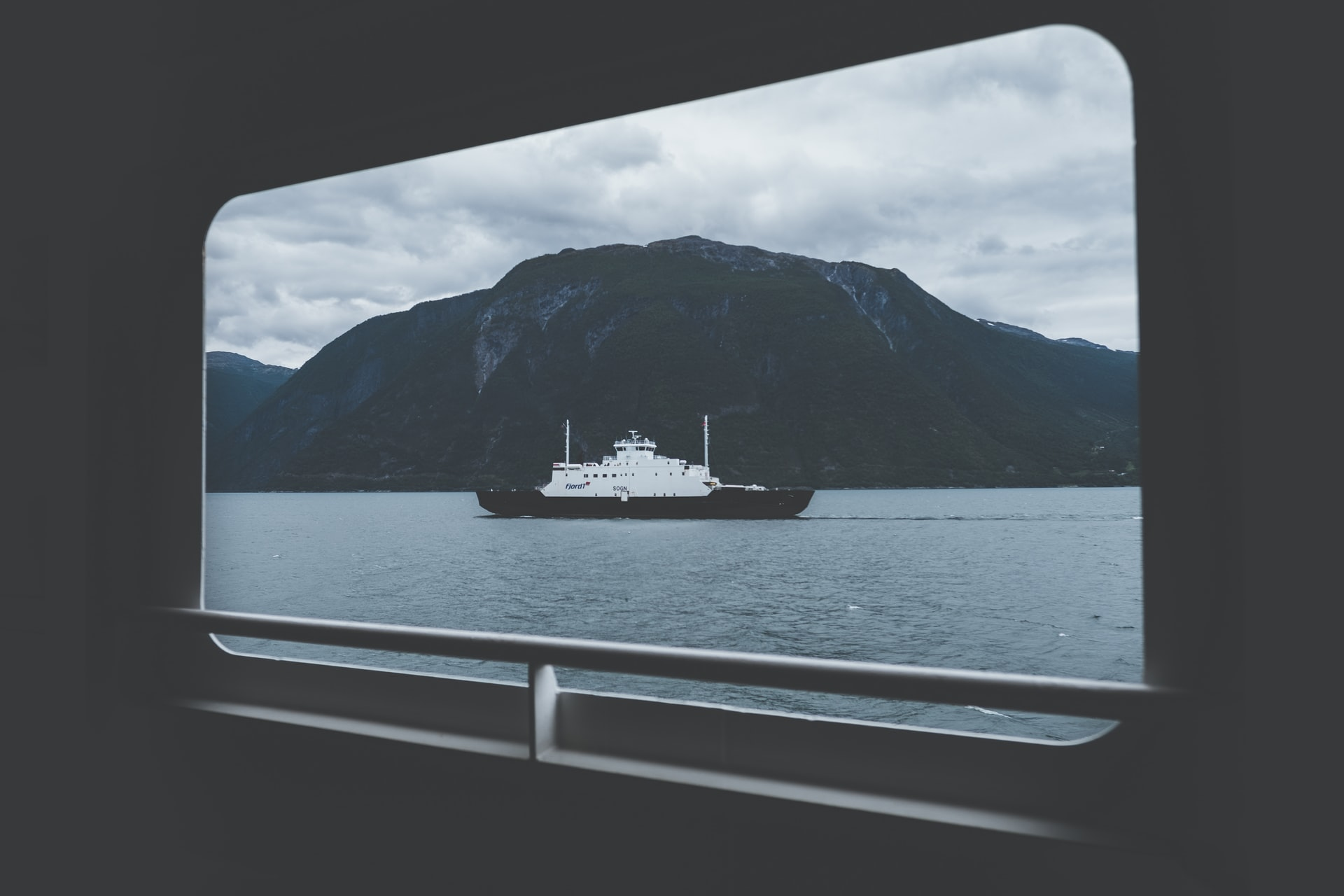Ship on a body of water in front of a mountain. Photo courtesy of Oskars Sylwan on Unsplash.