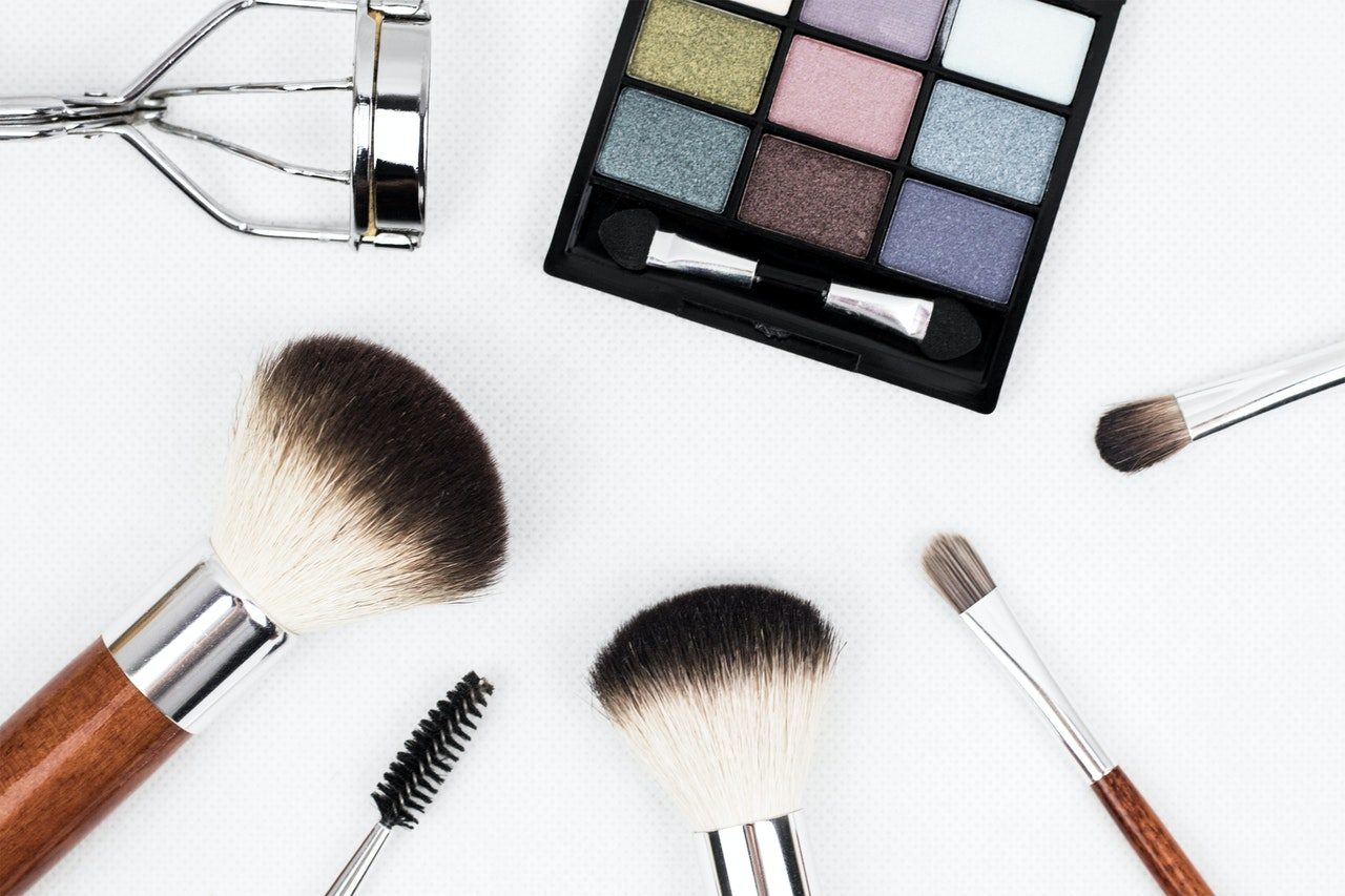 Makeup palette, assorted brushes, and an eyelash curler. Photo courtesy of Kinkate on Pexels.