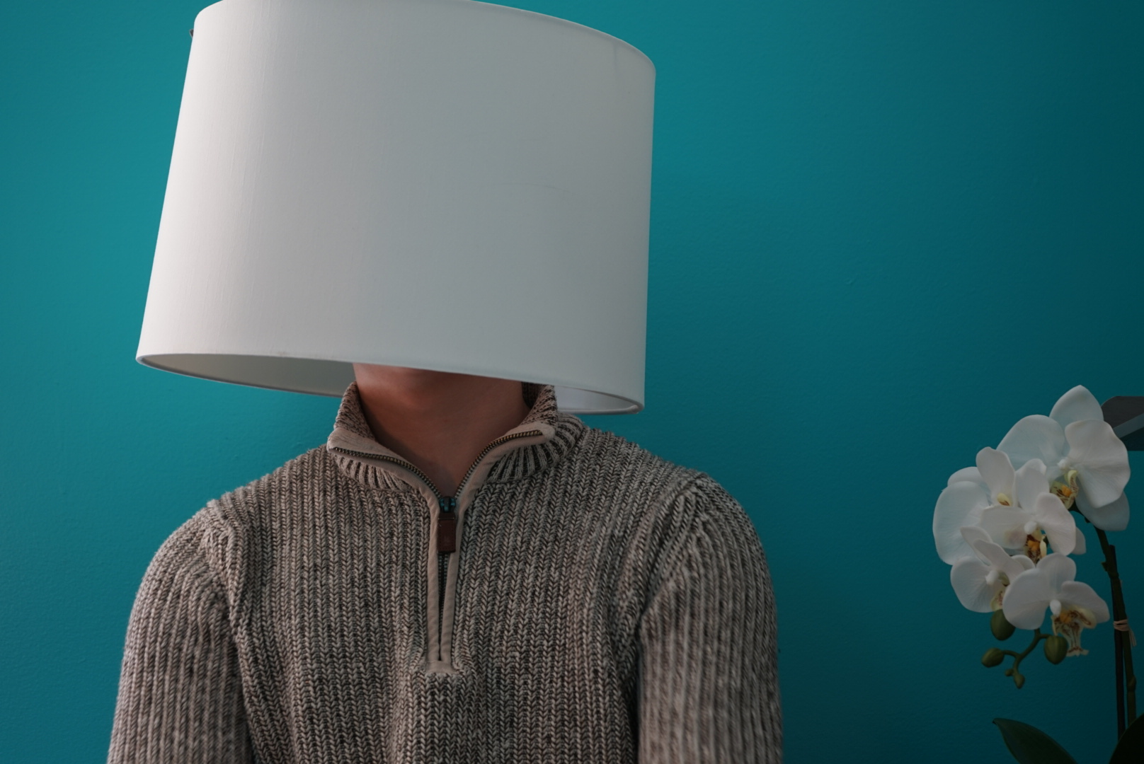 Person wearing a sweater with a lampshade over their head. Photo taken and provided by Nathan DeJesus.
