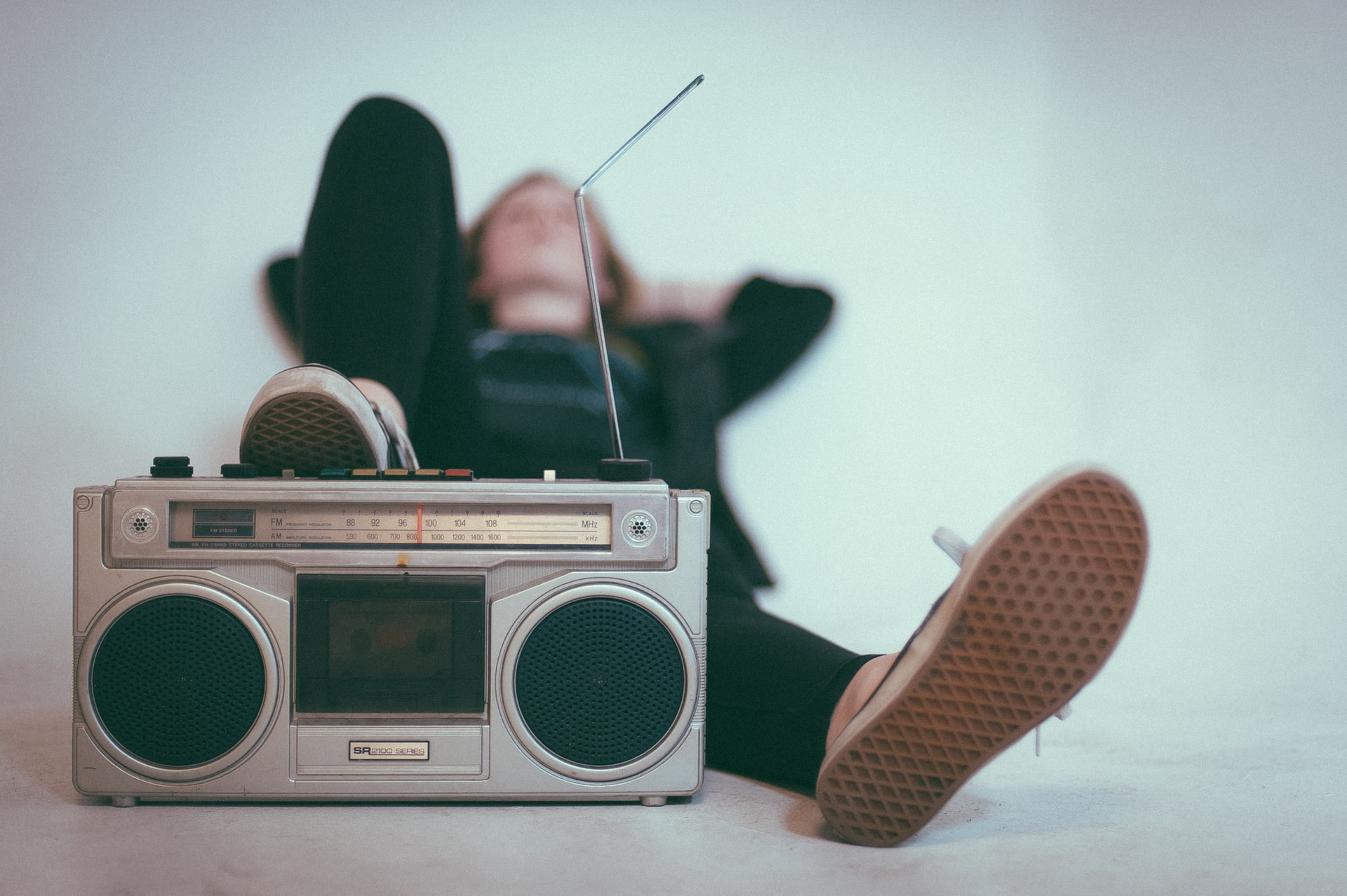 Woman laying on her back and resting her foot on a boombox. Photo courtesy of Eric Nopanen on Unsplash.