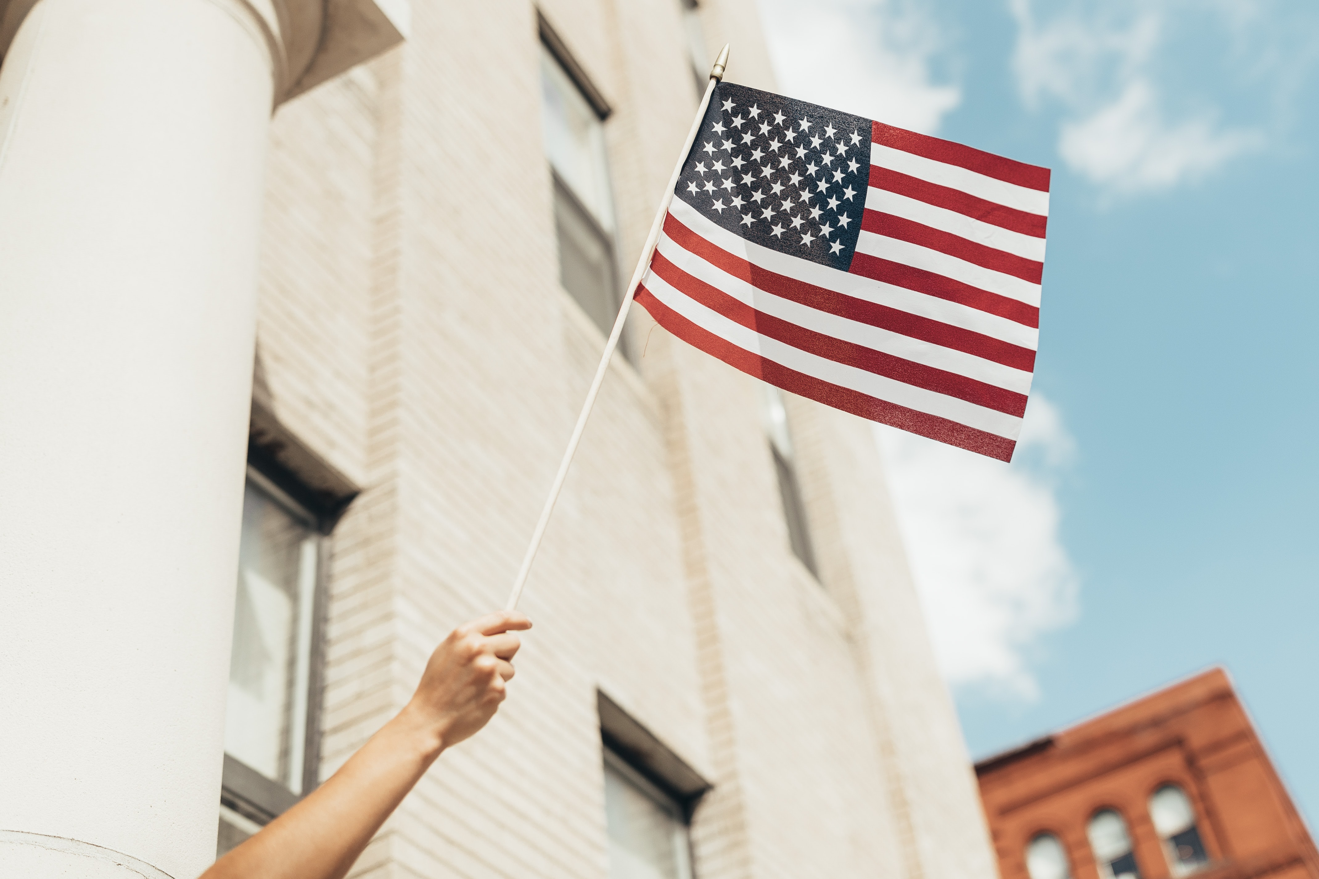A hand holds an American flag to the sky. Photo courtesy of Paul Weaver on Unsplash.