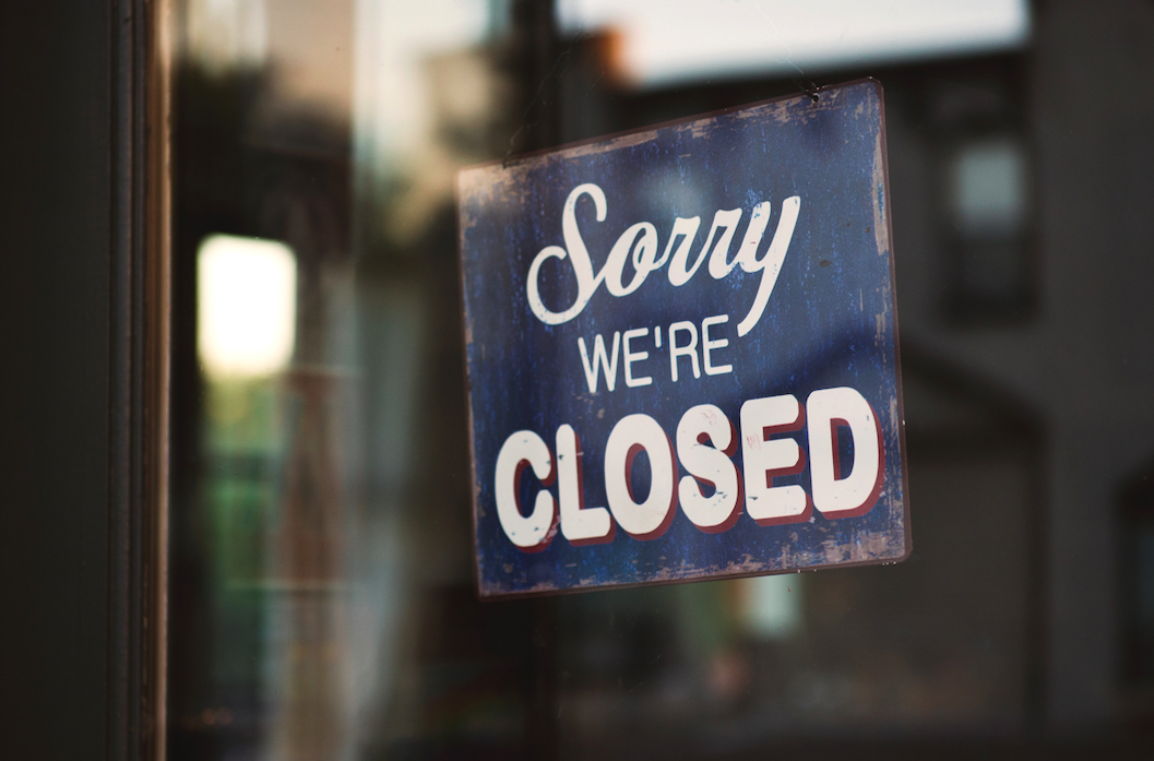 """Photo of """"Sorry we're closed"""" sign in a business's window. Image courtesy of Tim Mossholder via Unsplash."""
