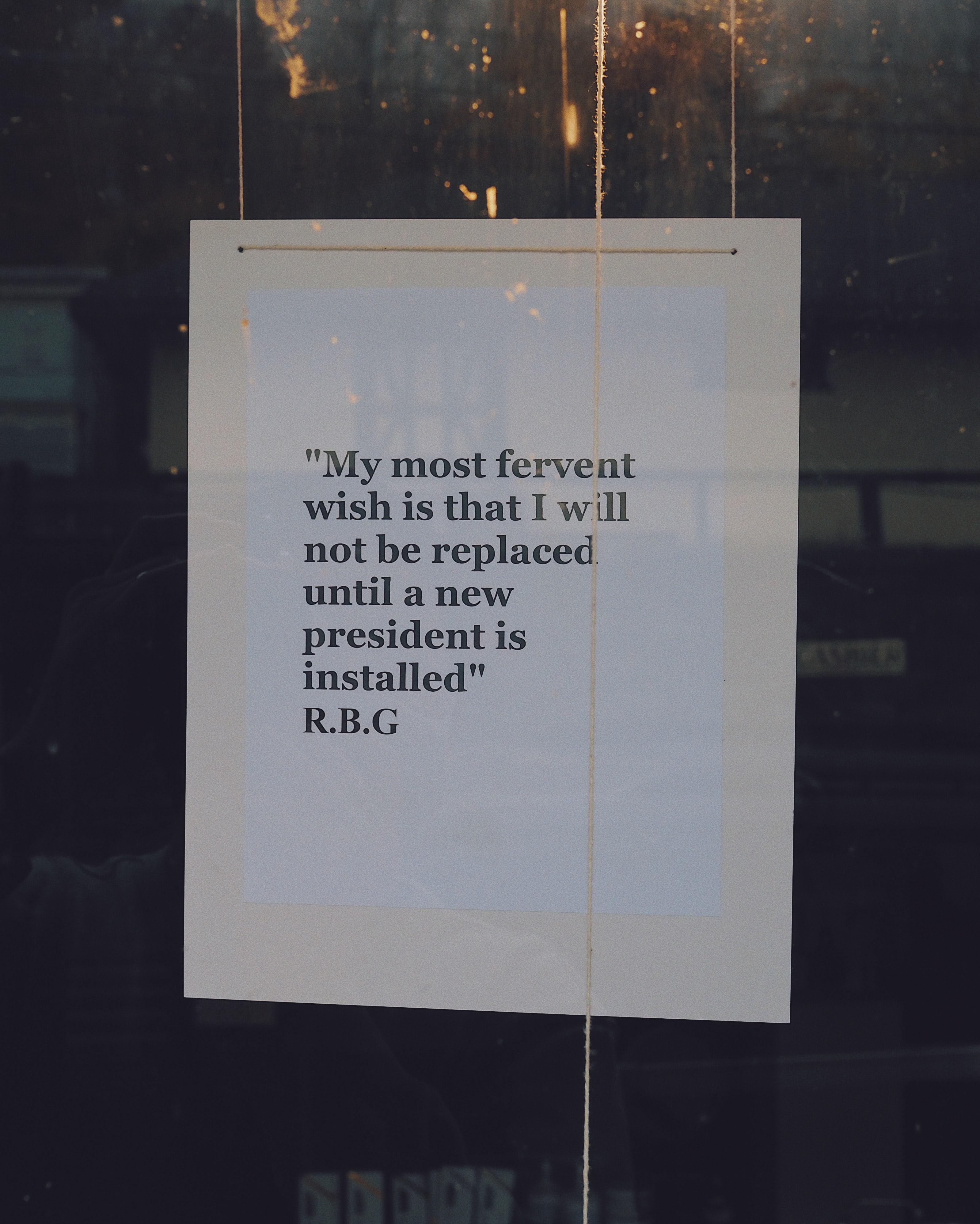 "Photo of a sign haging in a window that says, ""'My most fervent wish is that I will not be replaced until a new president is installed.' R.B.G."" Image courtesy of Greg Schmigel via Unsplash."
